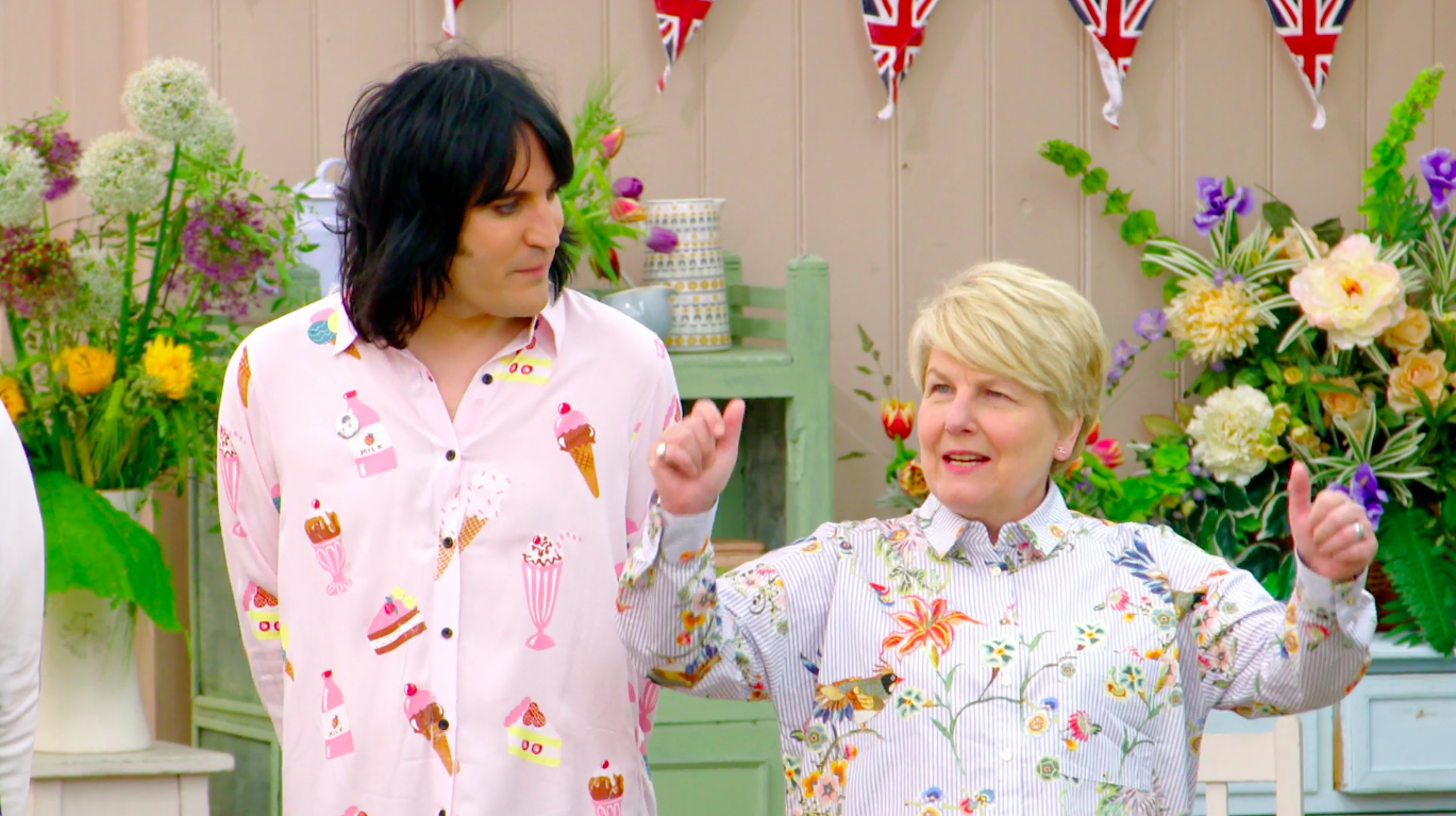 Noel Fielding and Sandi Toksvig, dressed in pastel clothes, standing in the tent.