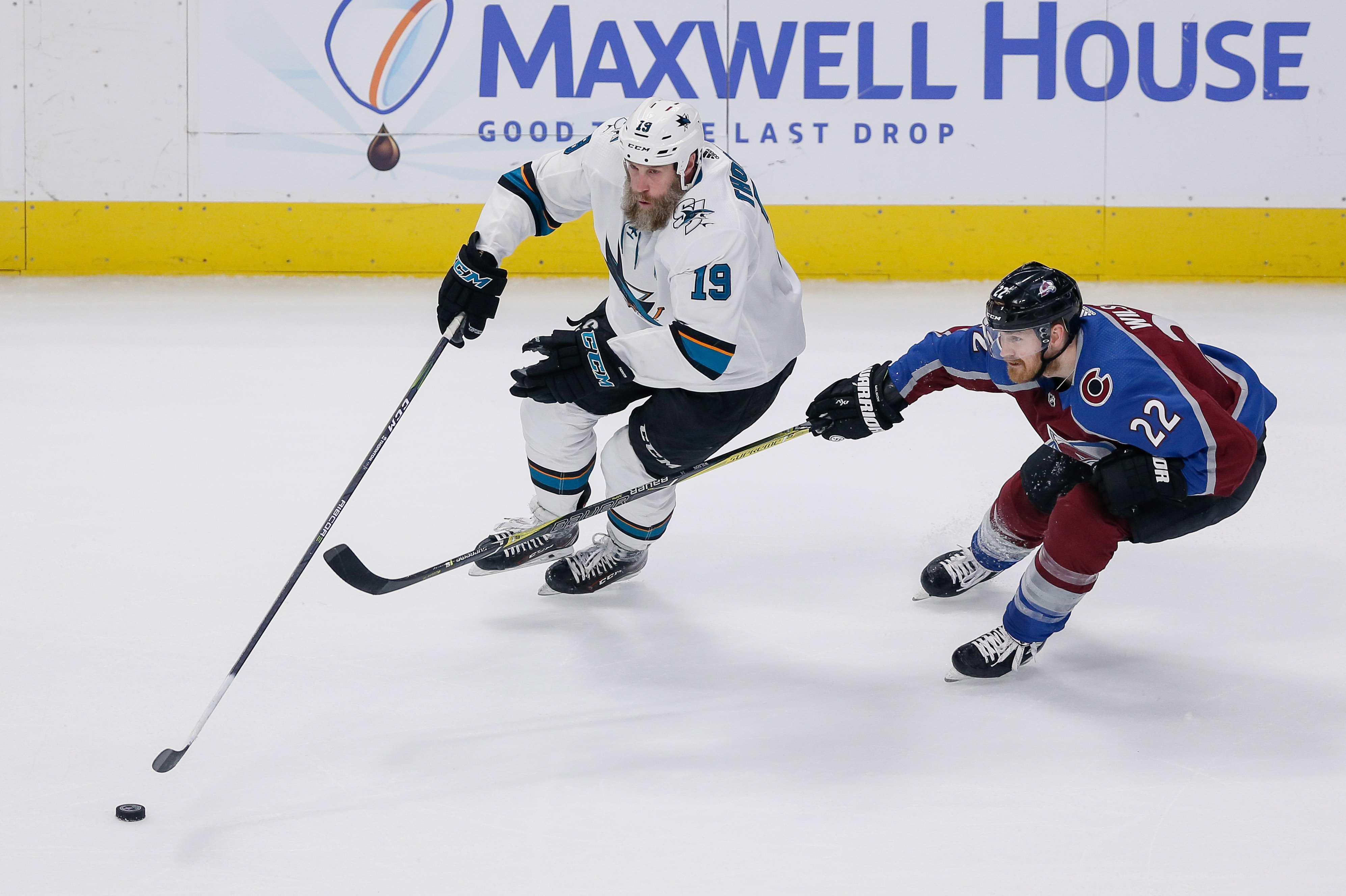 May 6, 2019; Denver, CO, USA; San Jose Sharks center Joe Thornton (19) controls the puck as Colorado Avalanche center Colin Wilson (22) defends in the third period in game six of the second round of the 2019 Stanley Cup Playoffs at the Pepsi Center.