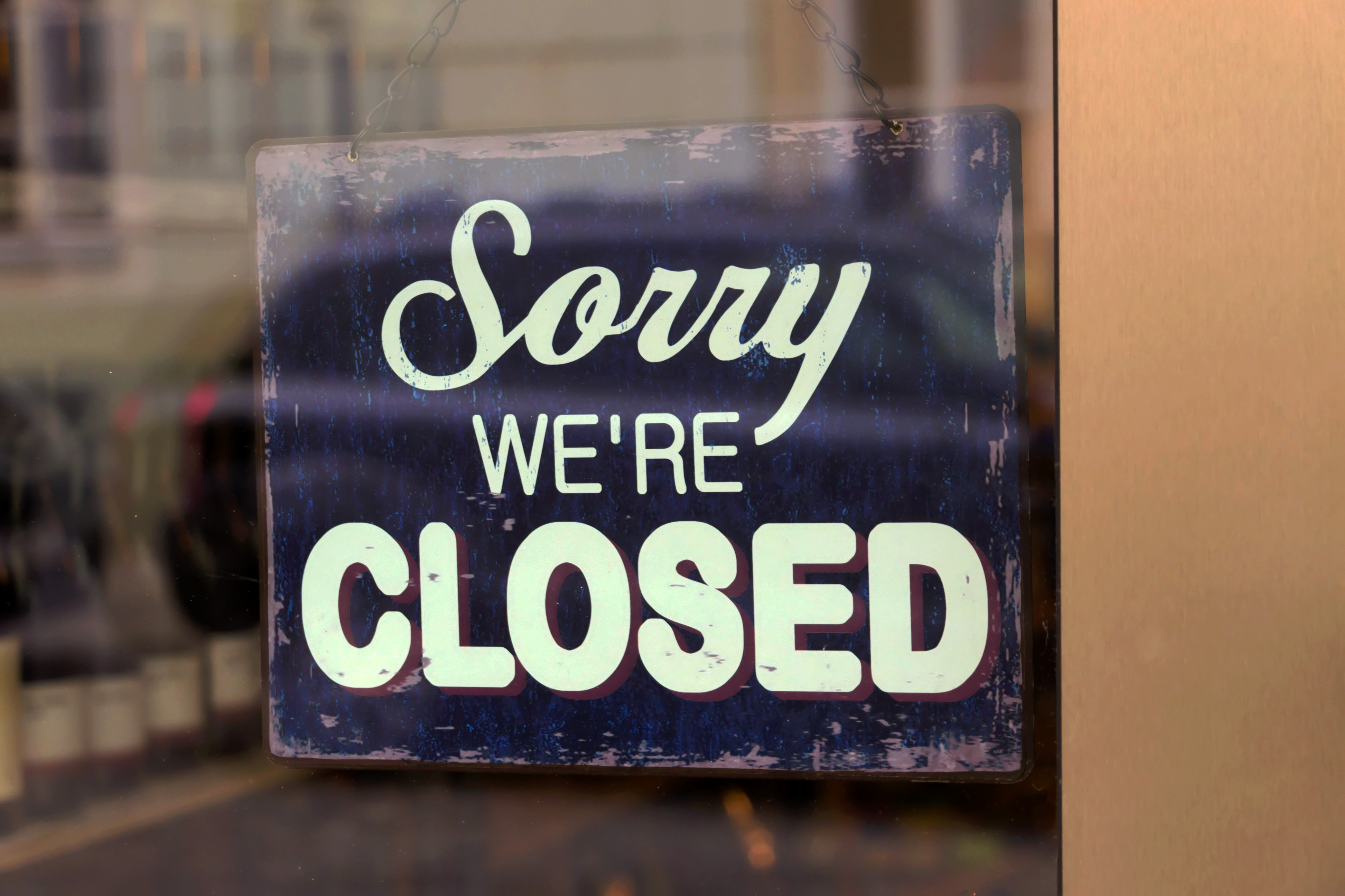 """A sign in a window reads """"Sorry We're Closed."""""""