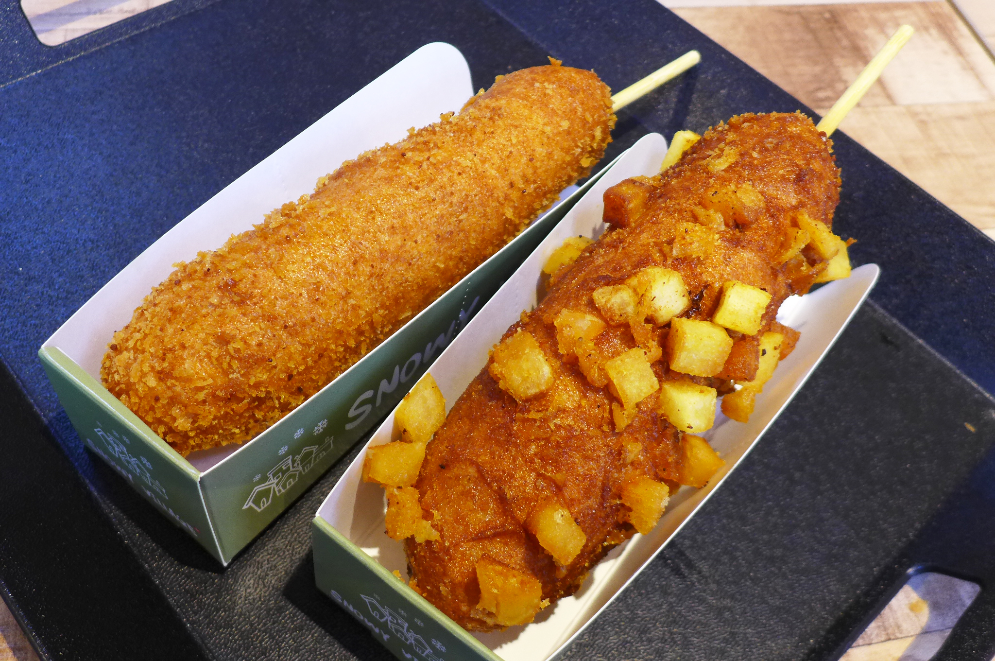 Two corn dogs, sticks protruding, one with potato cubes on the outside, the other without.