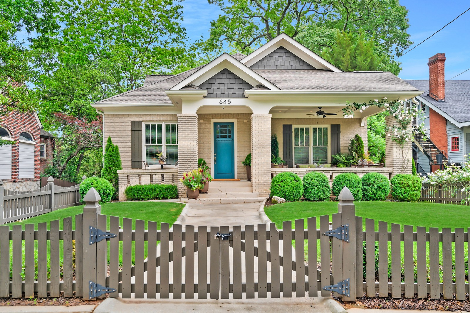 A beige brick bungalow behind lush green yard and a picket fence.