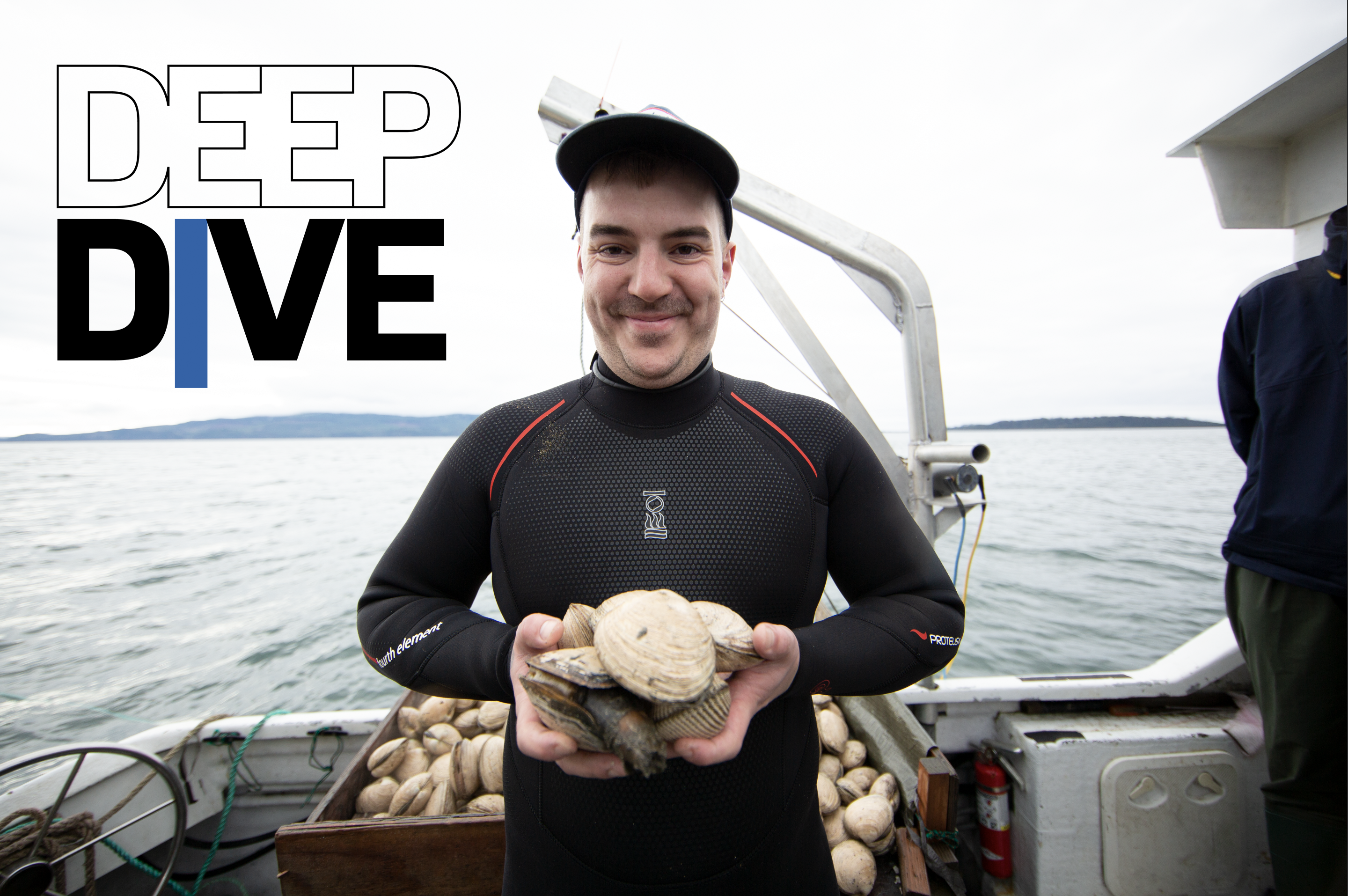 Jacob Harth, dressed in a wetsuit, stands on a fishing boat in Tillamook Bay. He's holding a big handful of butter clams with both hands.