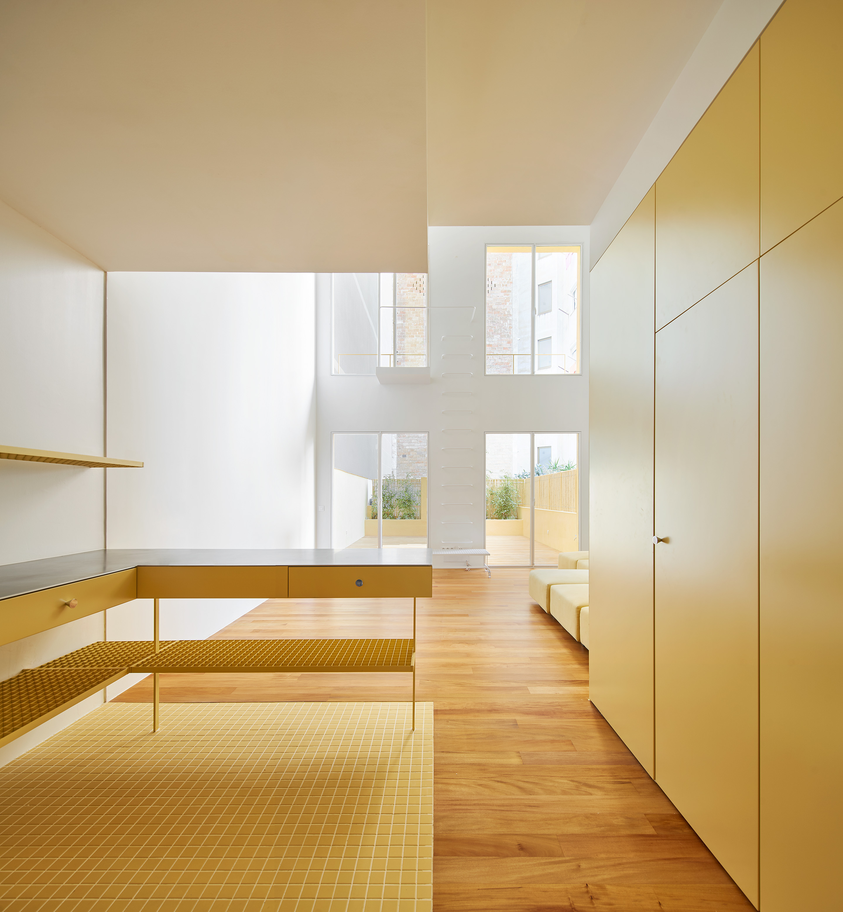 Bright apartment with large windows and yellow surfaces.