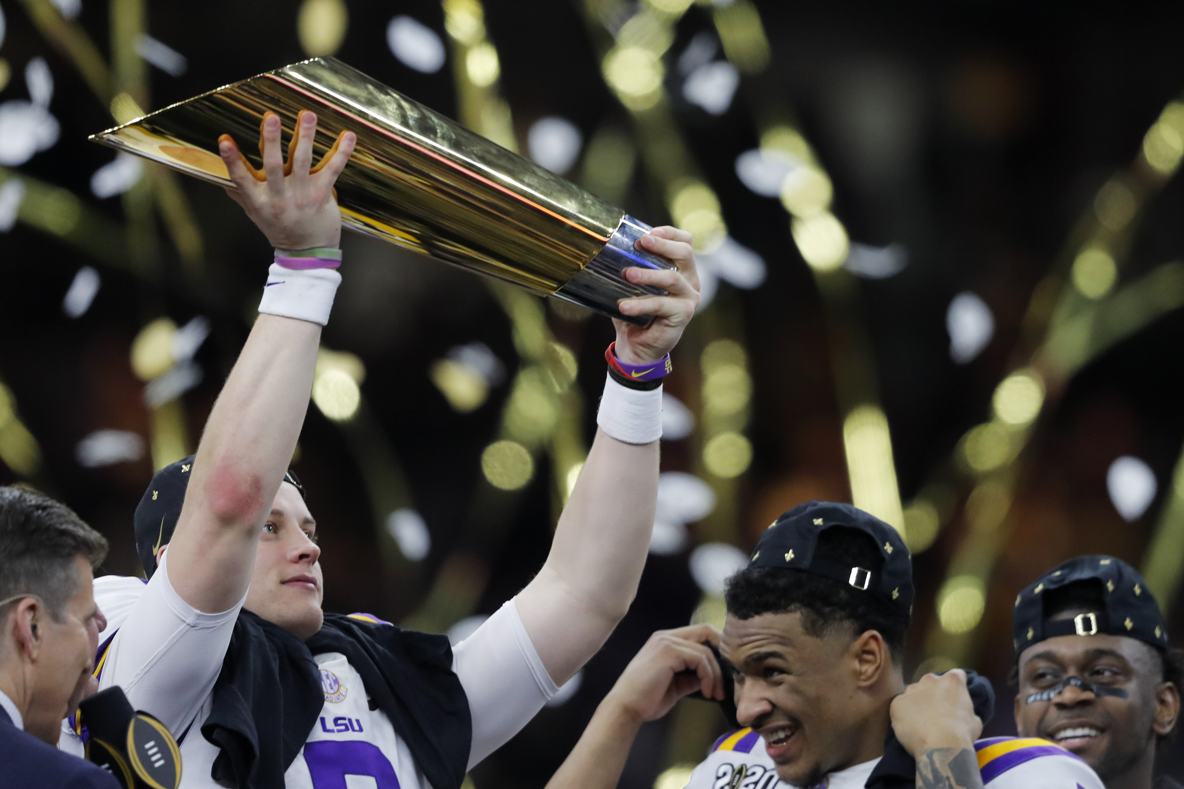 LSU quarterback Joe Burrow holds the trophy as safety Grant Delpit looks on after a NCAA College Football Playoff national championship game against Clemson, Monday, Jan. 13, 2020, in New Orleans. LSU won 42-25. (AP Photo/Gerald Herbert)