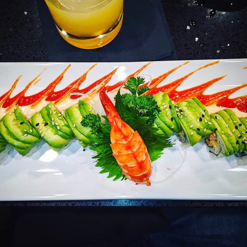 Avocado-covered sliced sushi with a lobster tail in the middle and red sauce splaying out