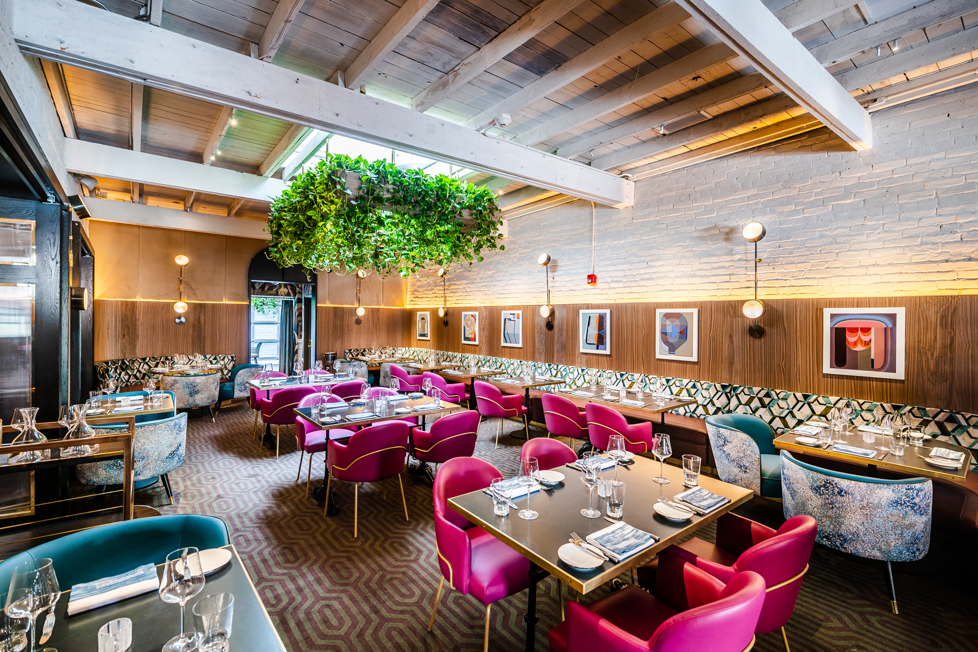 Cush pink chairs surrounding dining room tables in the middle of a main room covered in wood-lining, white brick, art, and green hanging plants at Annabelle