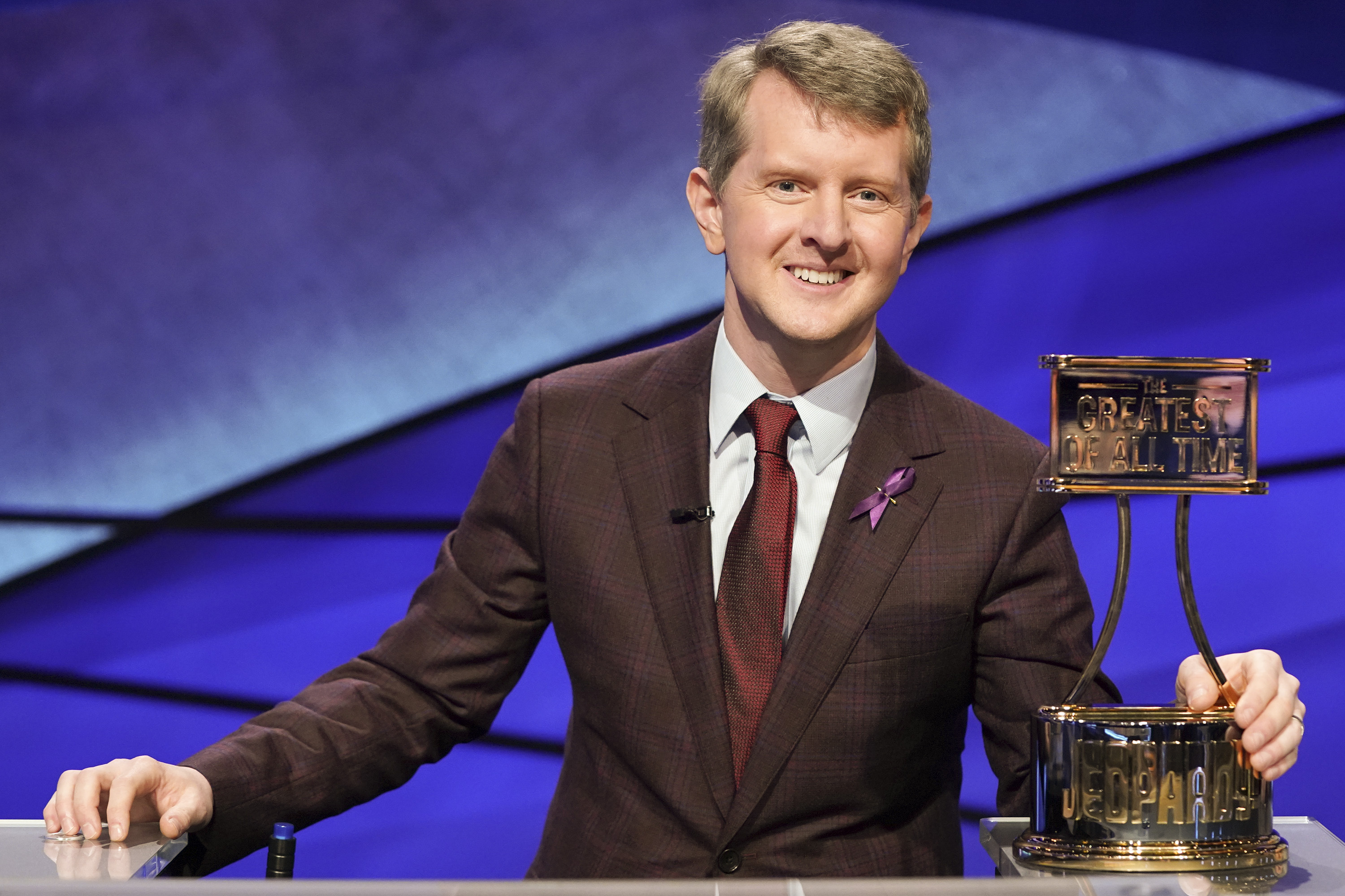 "This image released by ABS shows contestant Ken Jennings with a trophy on ""JEOPARDY! The Greatest of All Time."" Jennings, the veteran who beat young hotshot James Holzhauer and Brad Rutter, won the $1 million prize in the tournament that stretched out over four entertaining nights on ABC's prime-time schedule."