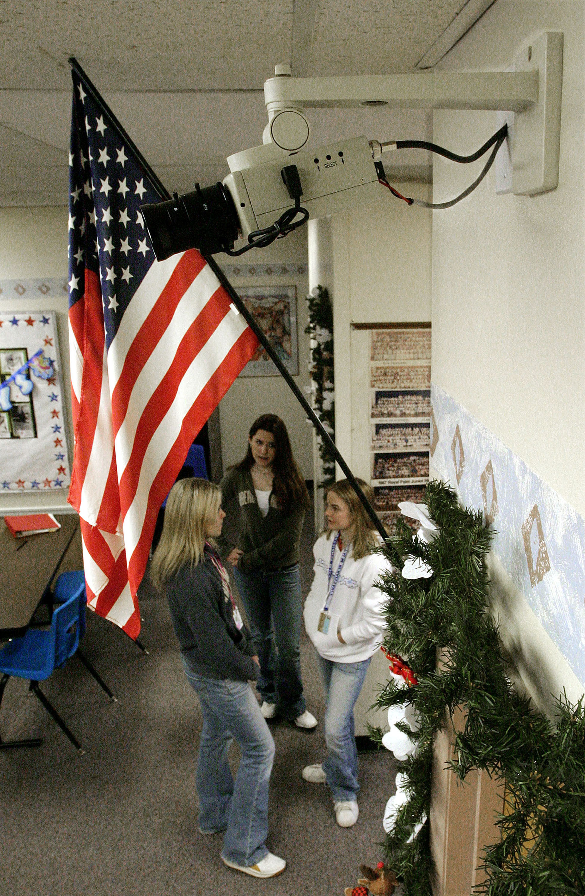 Students stand in a classroom beneath a US flag and near a facial-recogniton-enabled camera at a school in Phoenix, Arizona.