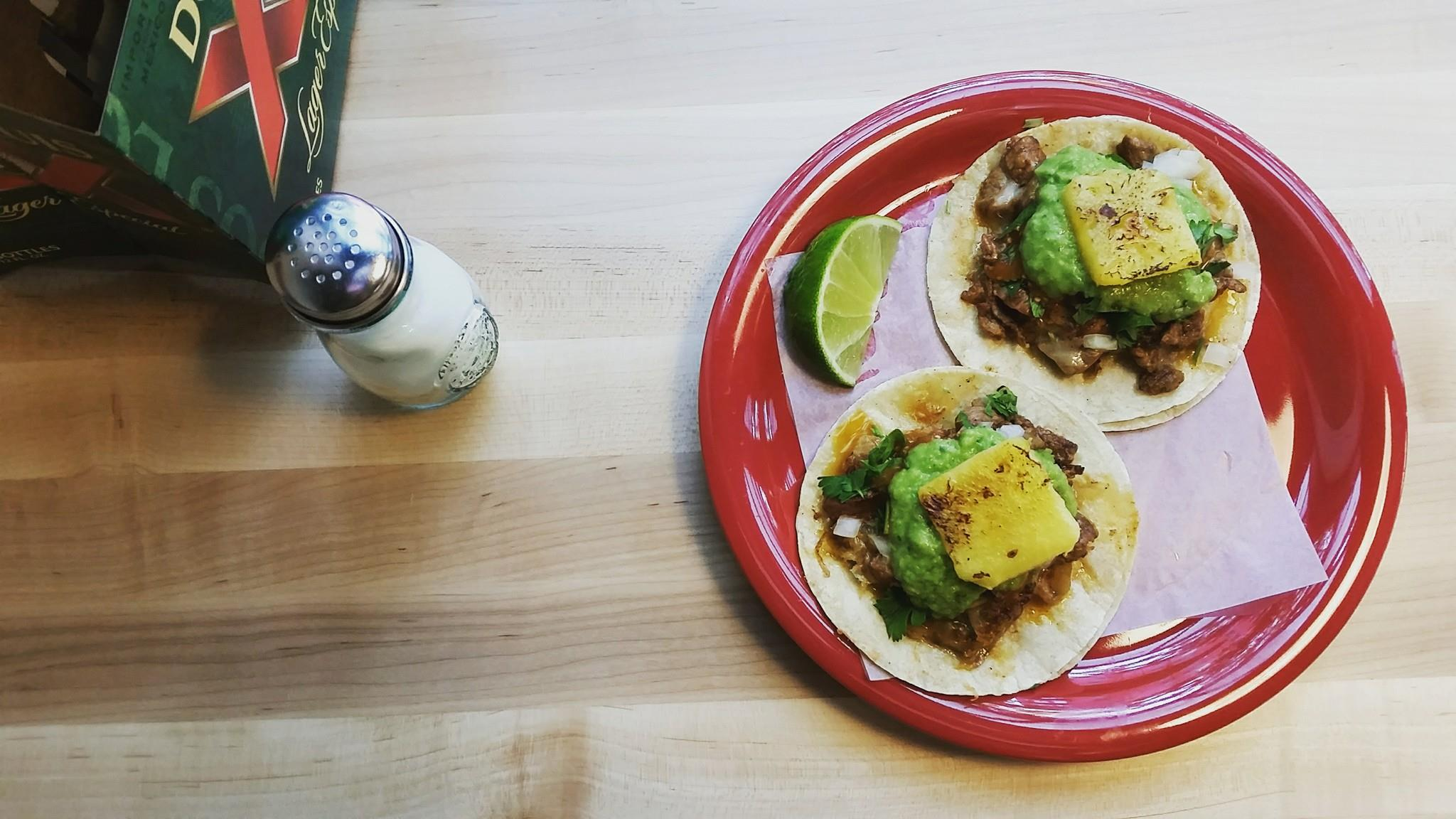 A bird's eye view of adobada pork tacos with guacamole and slices of pineapple on a wooden table, alongside a salt shake.