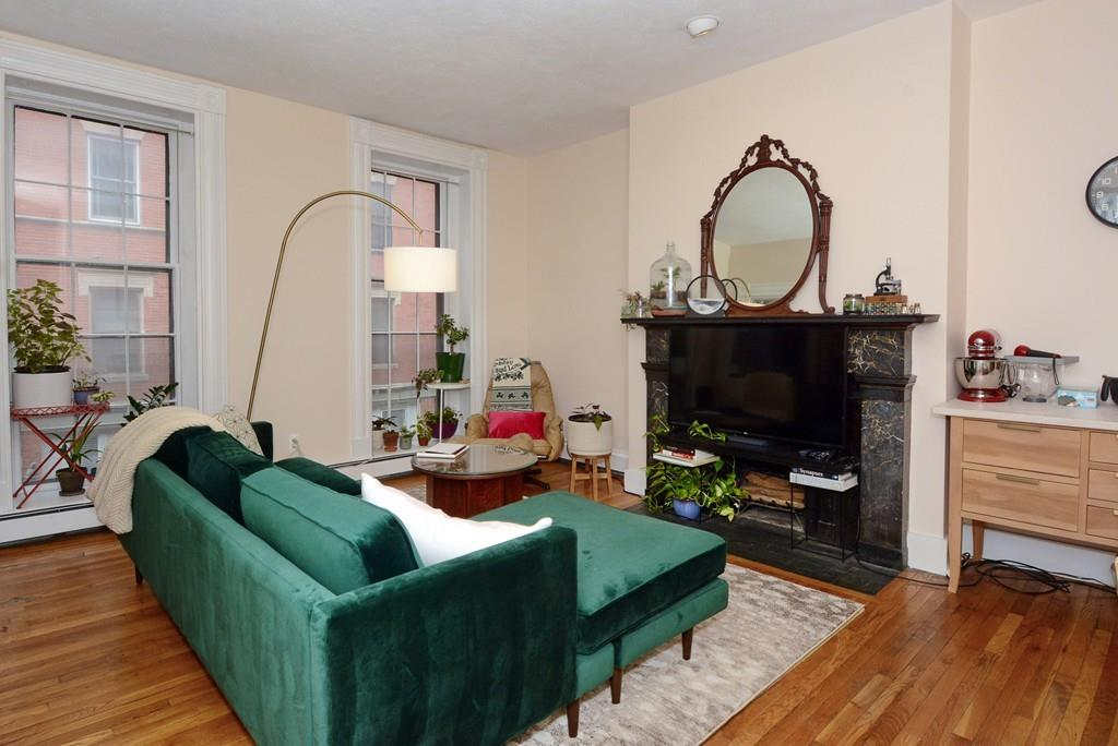 A small living room with a large couch facing a large fireplace, and there's a hanging lamp over the couch.