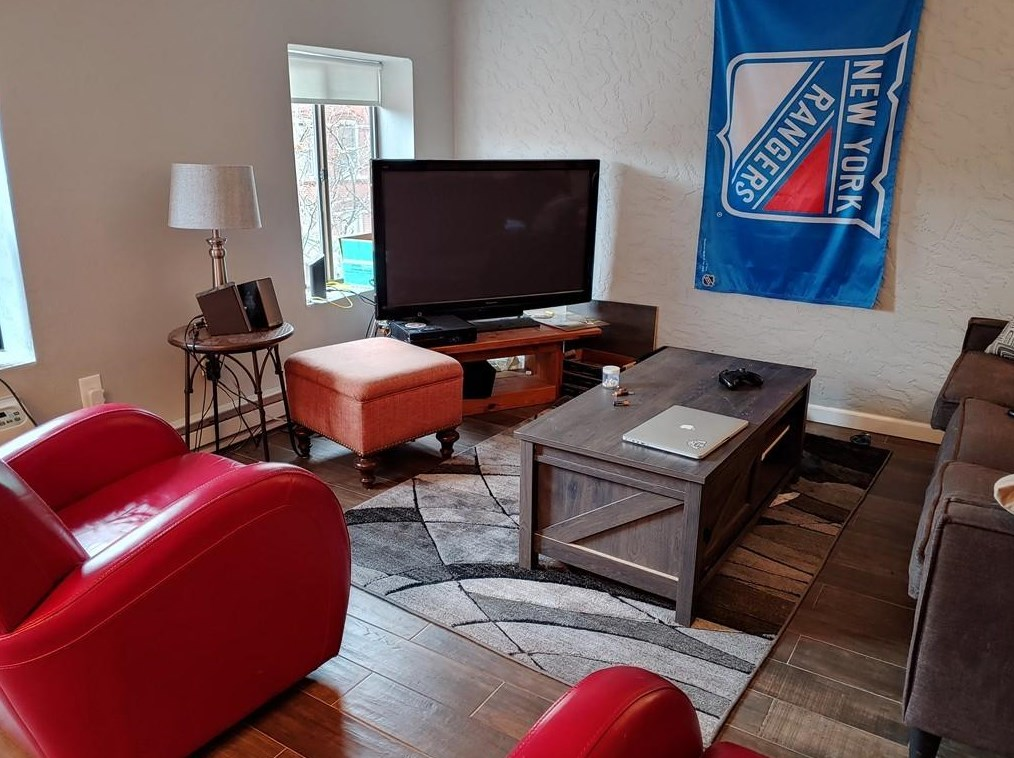 A small living room with furniture and a New York Rangers banner on the wall.