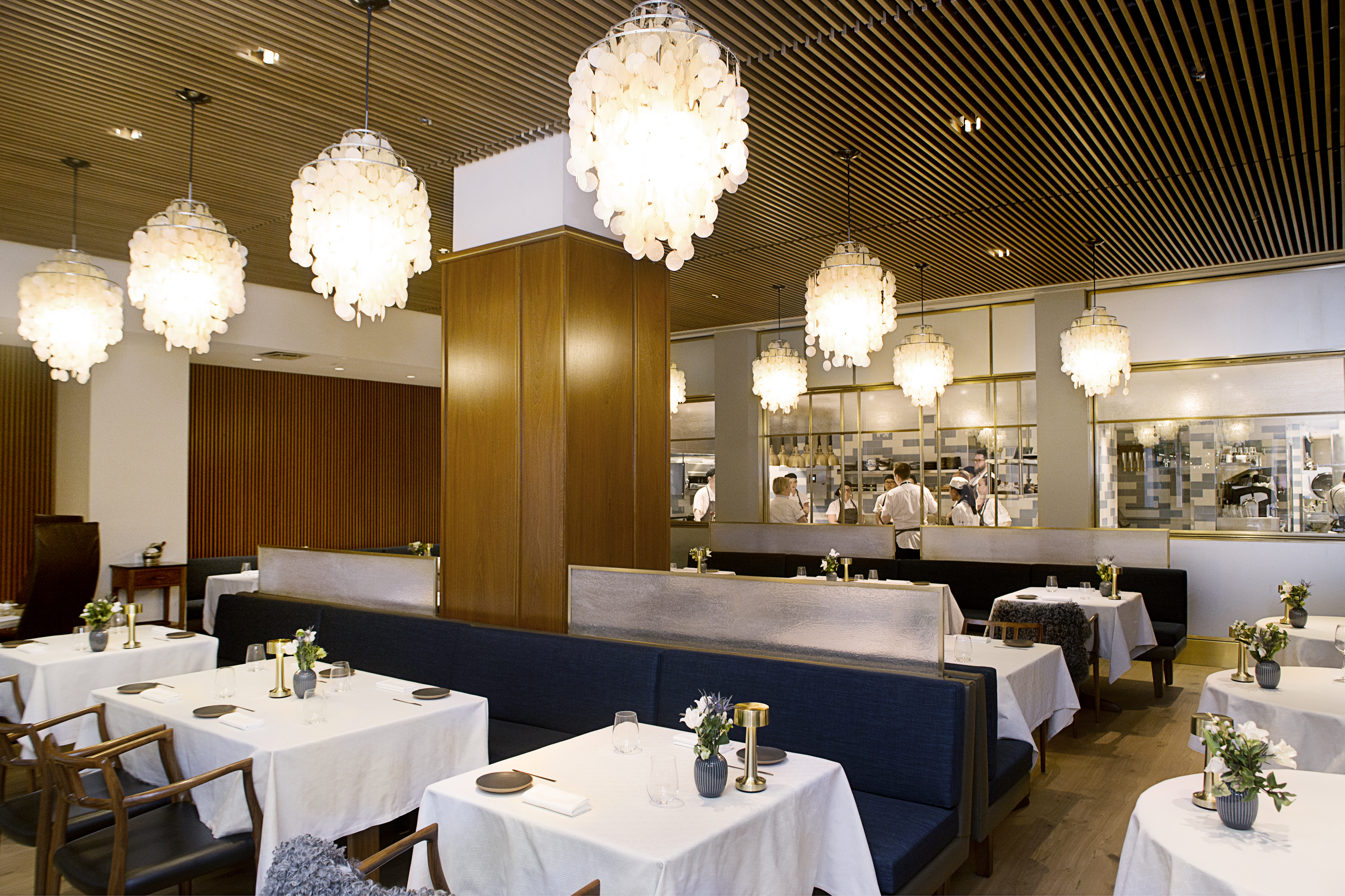 A dining room with white tablecloths, banquettes, and white chandeliers.