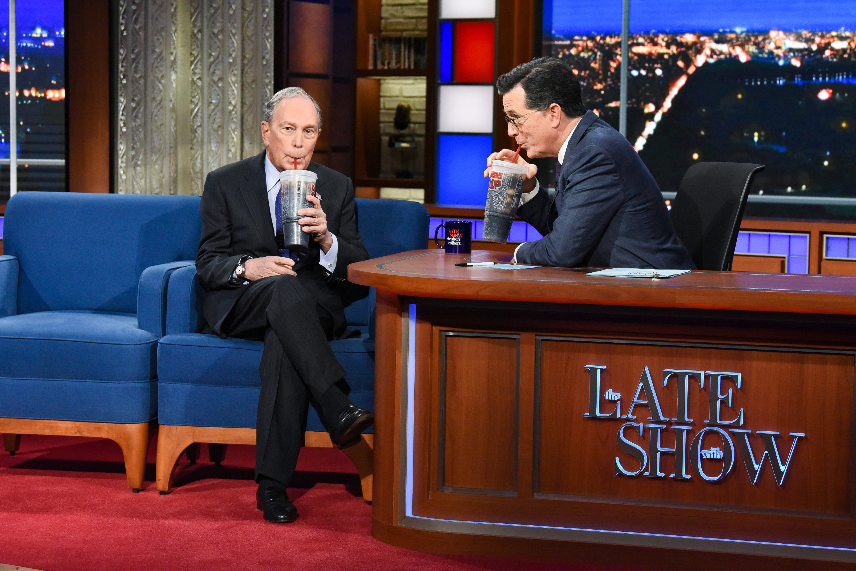 Michael Bloomberg and Stephen Colbert sip on giant sodas.