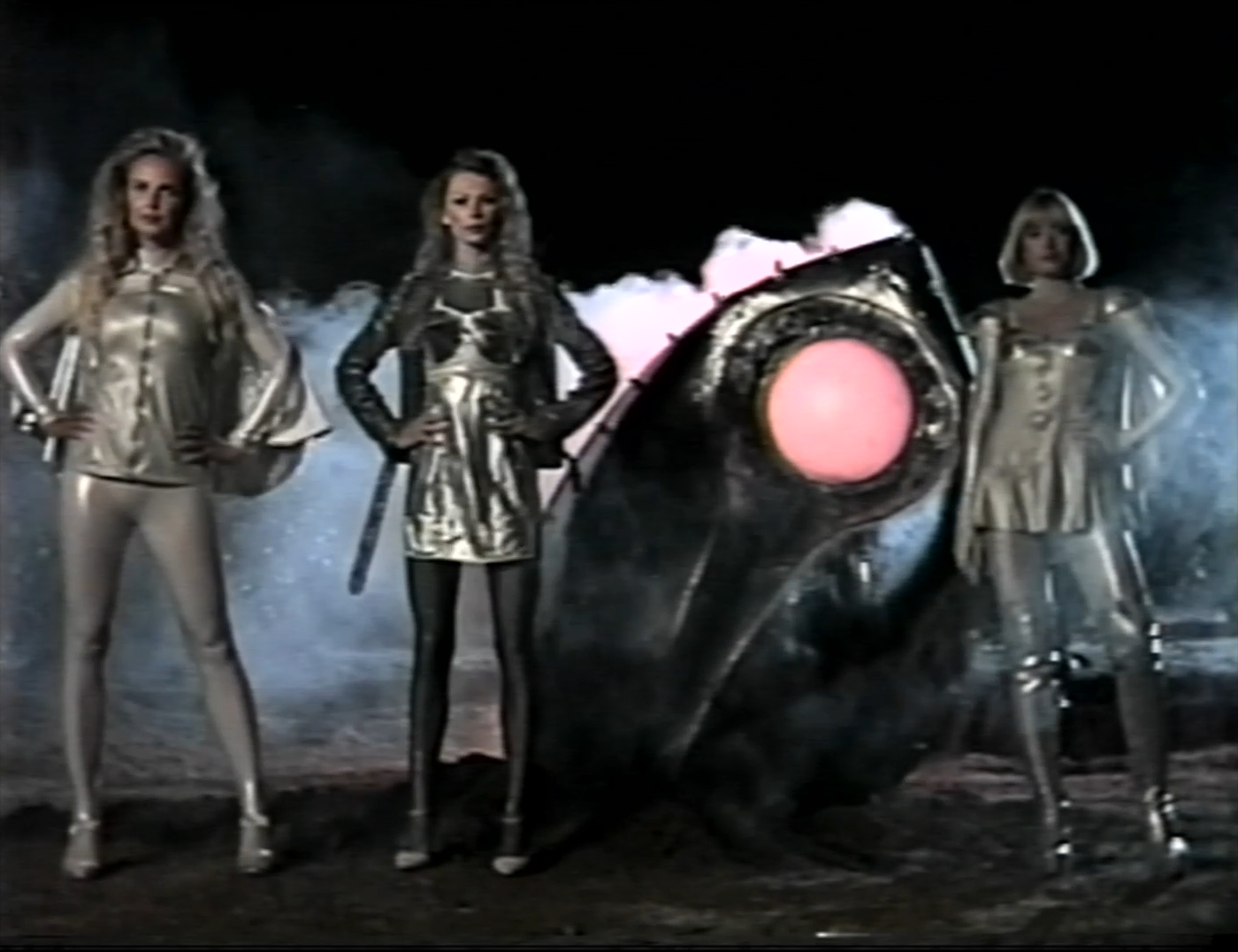 Three women in silver bodysuits stand next to a crashed spaceship.
