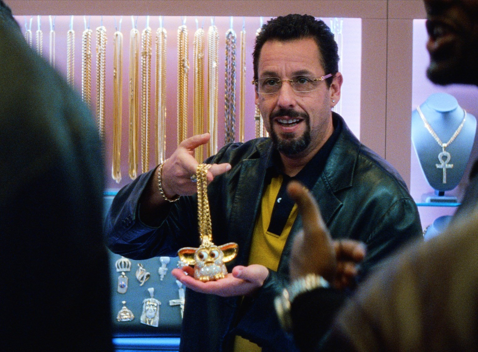 adam sandler's howard holds up a diamond-encrusted furby from behind a jewelry shop counter