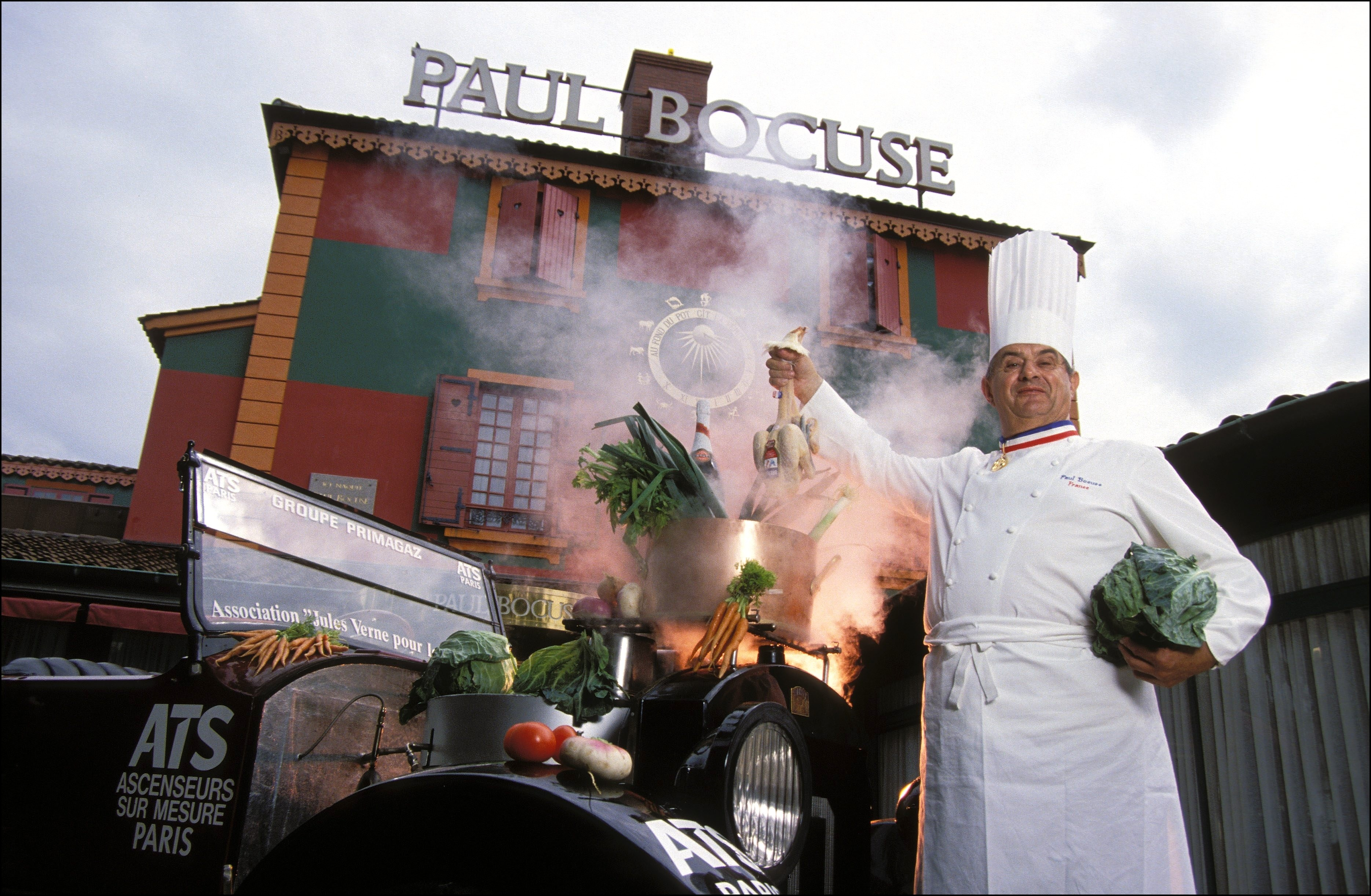 Paul Bocuse standing in front of his namesake restaurant.