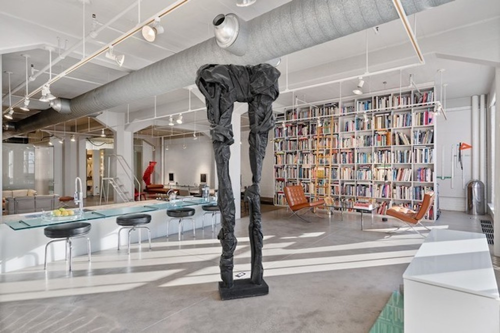A large metal sculpture resembling a pair a pants stands in the middle of an open room with modern furniture and a dining area with a low glass counter and four squat stools.