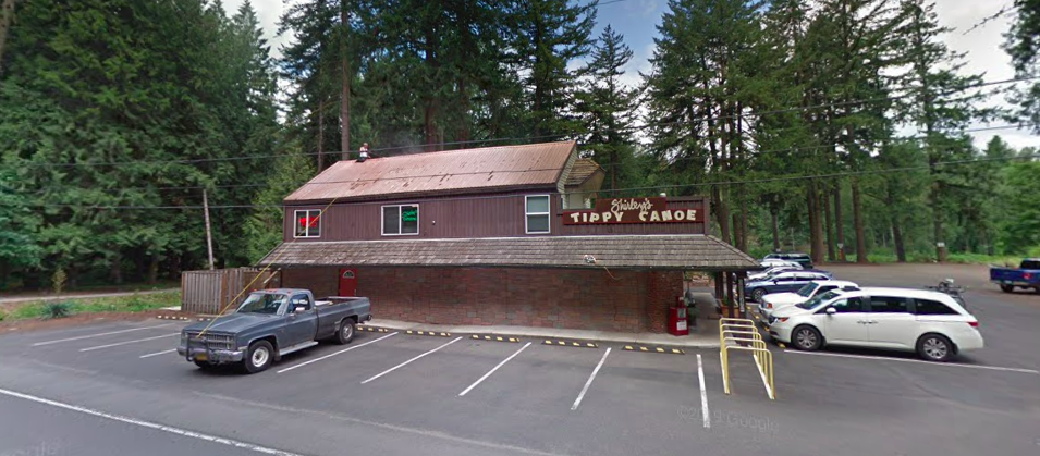 "A brown, wood-paneled restaurant sits on a summery day with a few cars in its small wraparound parking lot. A sign reading ""Shirley's Tippy Canoe"" sticks up from the restaurant's awning."