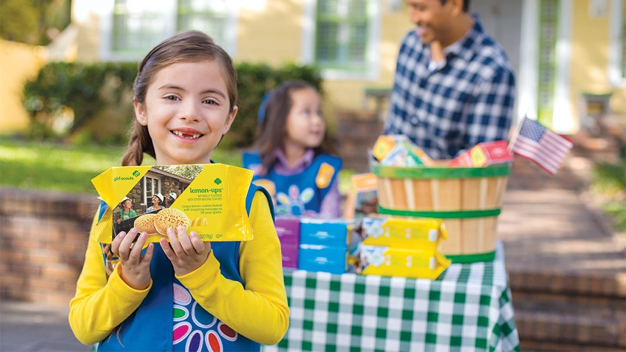 A Girl Scout selling cookies.