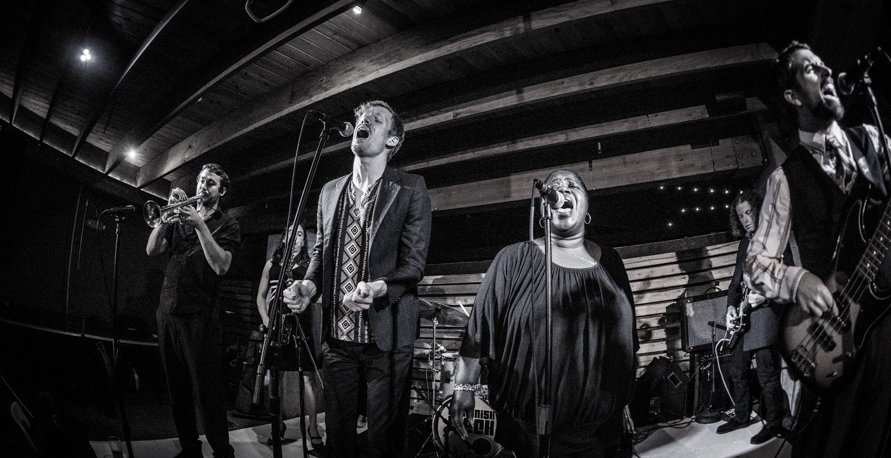 A woman sings into a microphone next to a tall man, under wood beams of Romtom's outdoor patio