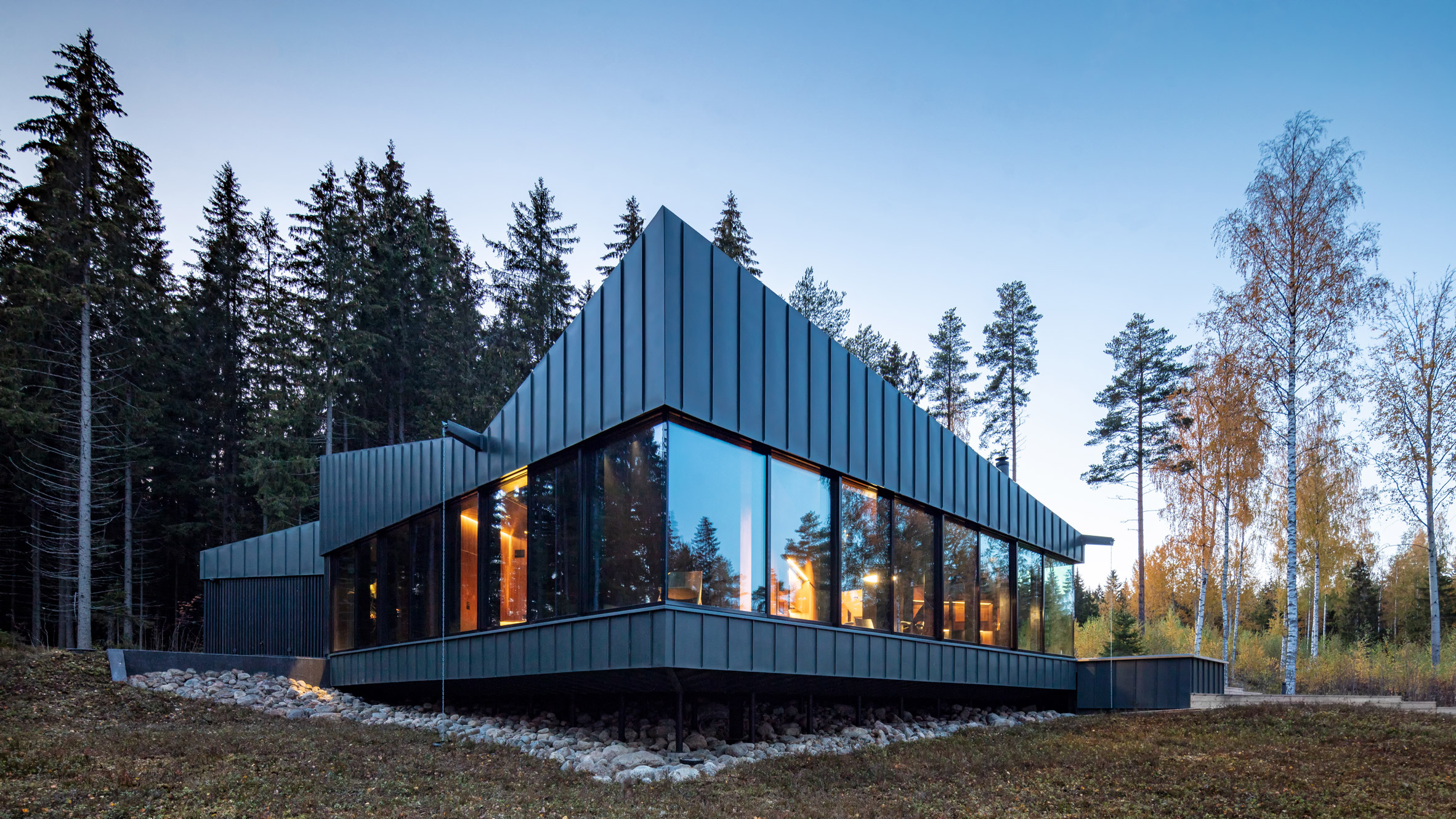 Home clad in windows and dark zinc siding.