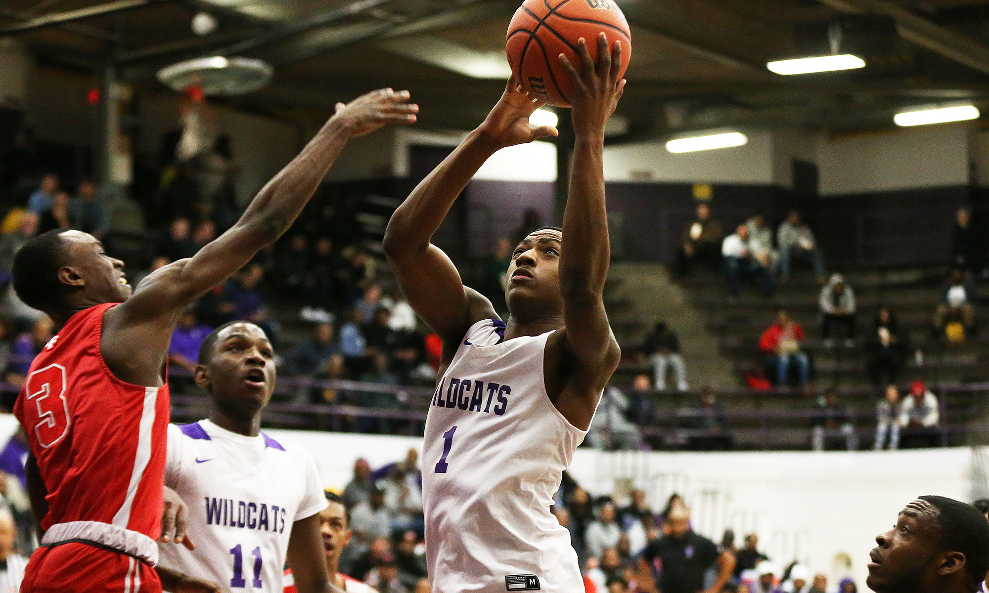 Thornton's Demarco Minor (1) grabs a rebound and puts it back up as the Wildcats play Homewood-Flossmoor.