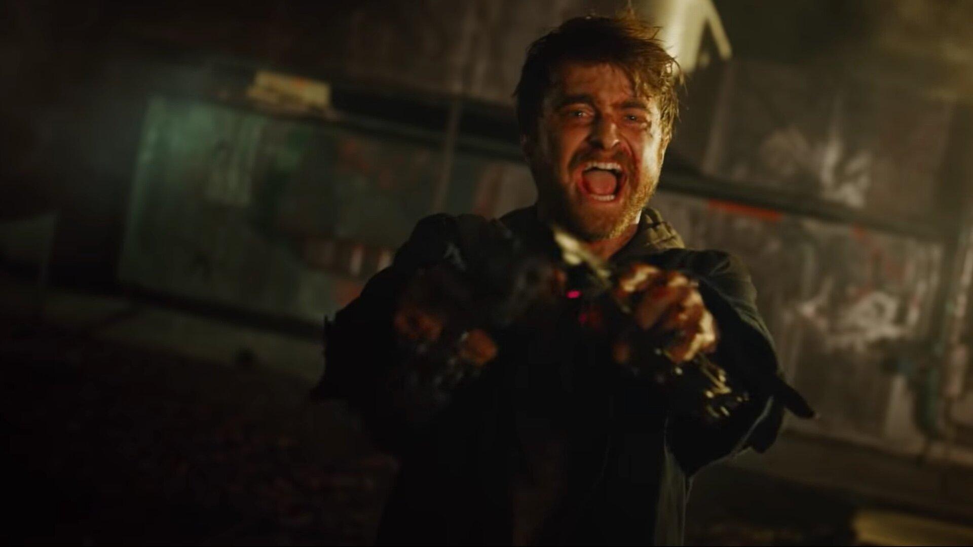 Radcliffe screams as he points two guns.