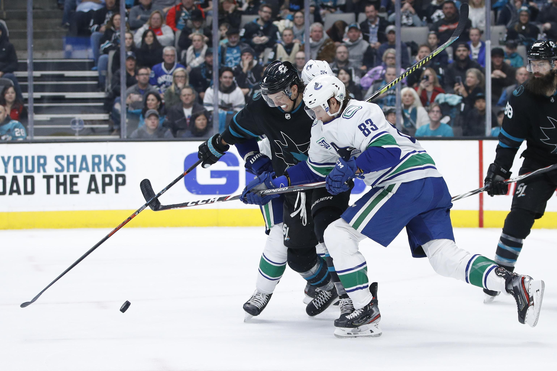 Dec 14, 2019; San Jose, CA, USA; San Jose Sharks defenseman Brenden Dillon (4) and Vancouver Canucks center Jay Beagle (83) battle for the puck during the third period at SAP Center at San Jose.