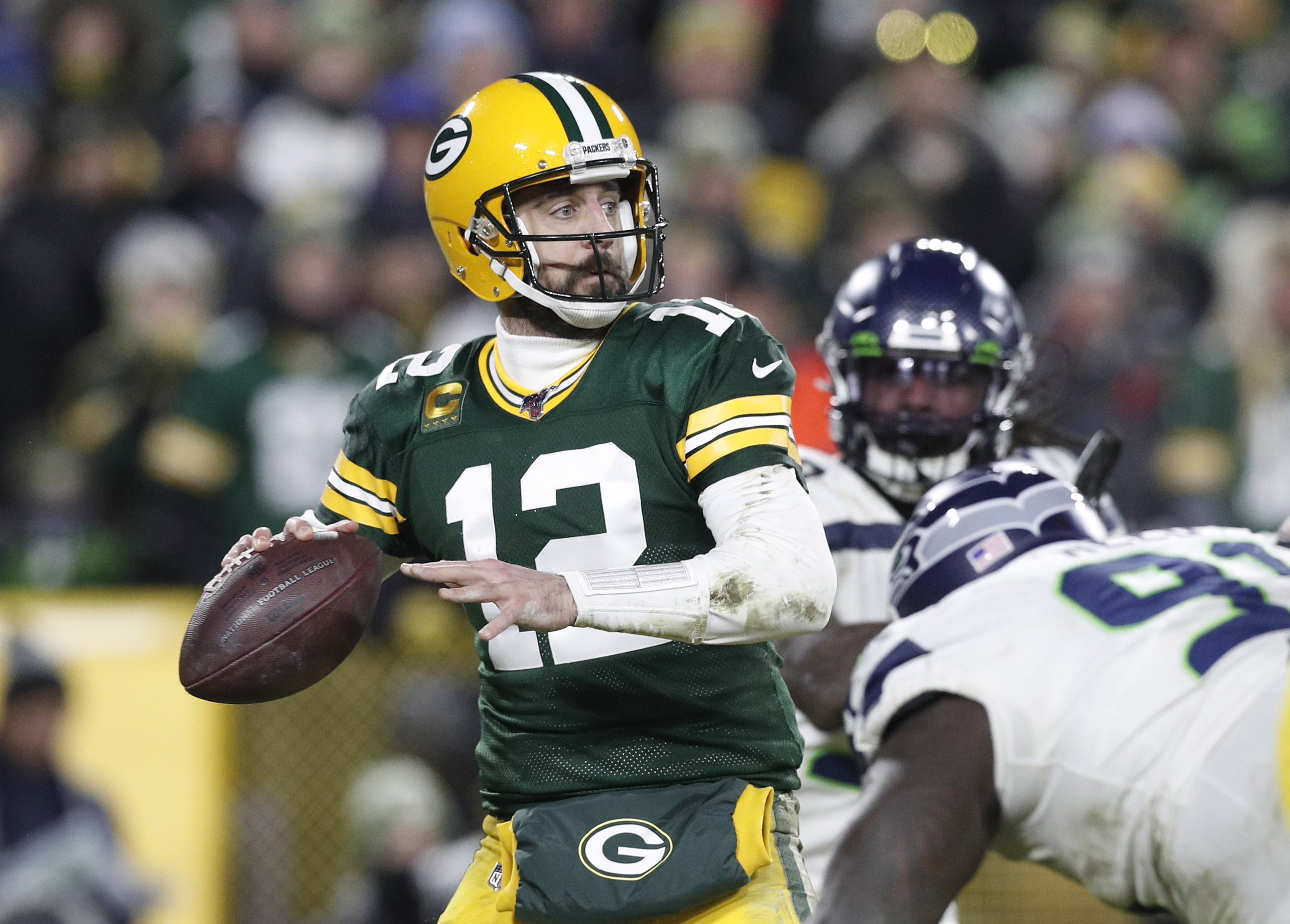 Green Bay Packers quarterback Aaron Rodgers throws a pass against the Seattle Seahawks in the fourth quarter of a NFC Divisional Round playoff football game at Lambeau Field.