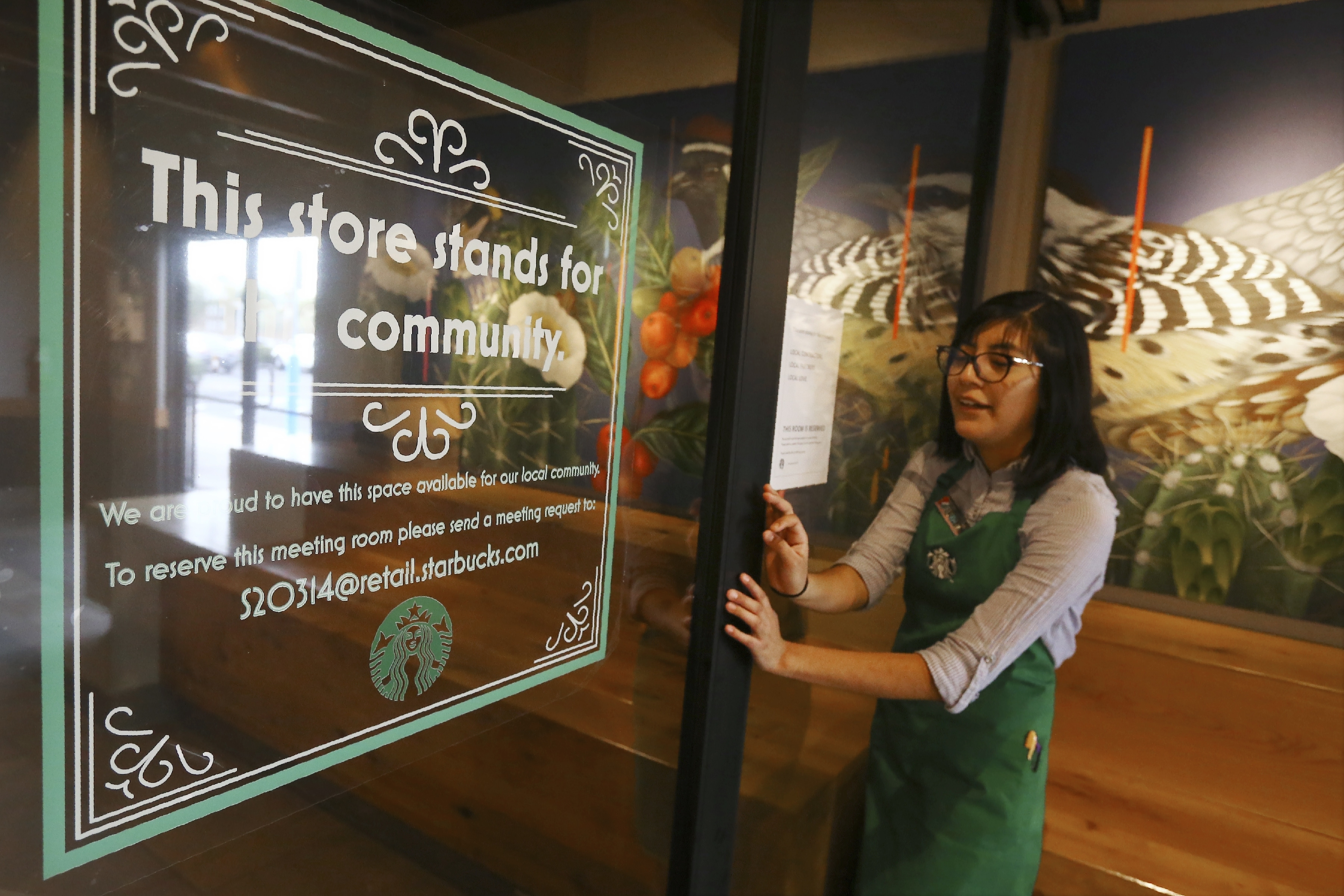 Belith Ariza, a barista trainer at Starbucks, opens the doors to the community meeting space at a local Starbucks Community Store, in Phoenix. The Seattle-based company plans to open or remodel 85 stores by 2025 in rural and urban communities across the U.S.