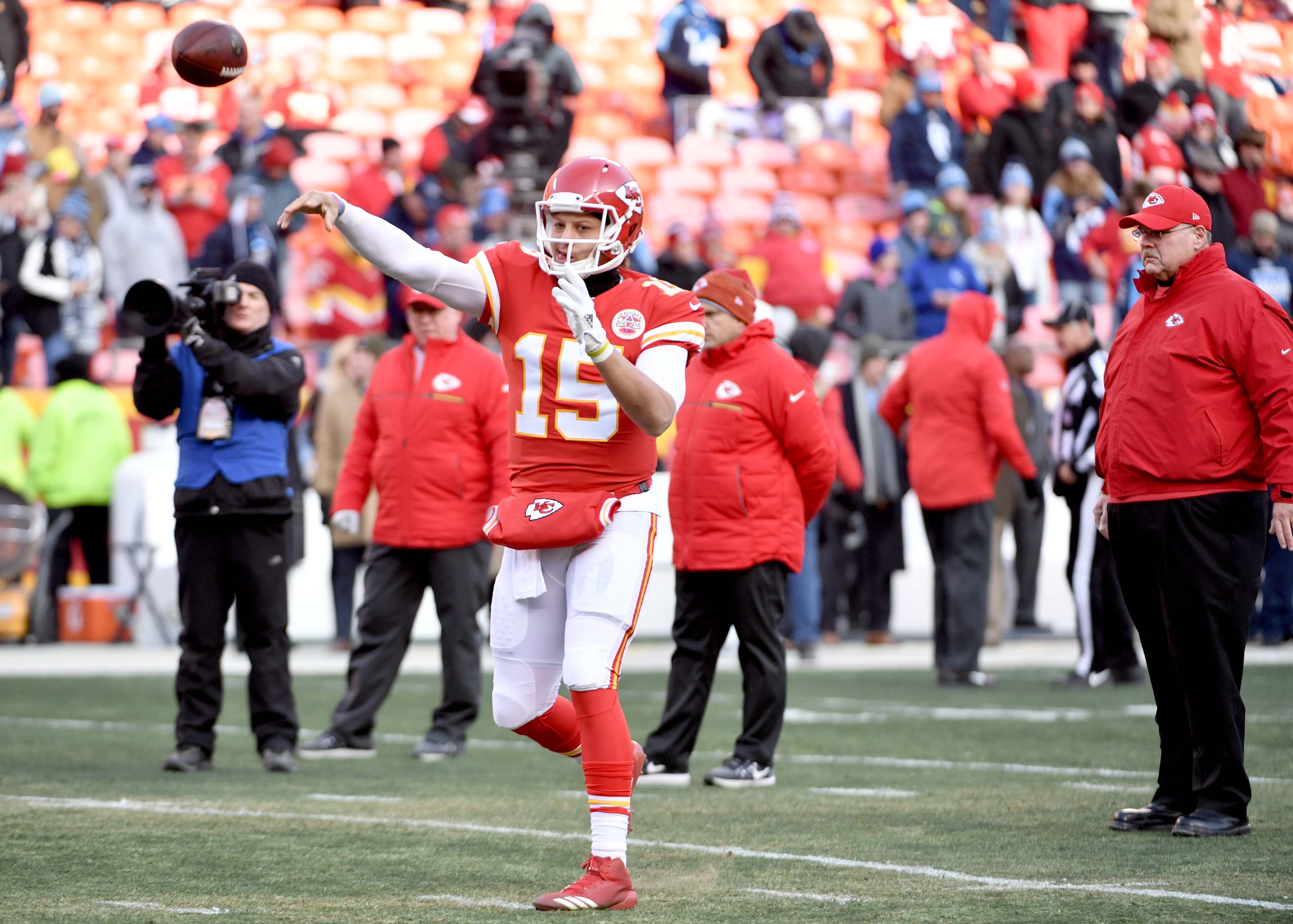 Kansas City Chiefs quarterback Patrick Mahomes warms up as head coach Andy Reid watches before the game against the Tennessee Titans in the AFC Wild Card playoff football game at Arrowhead stadium.