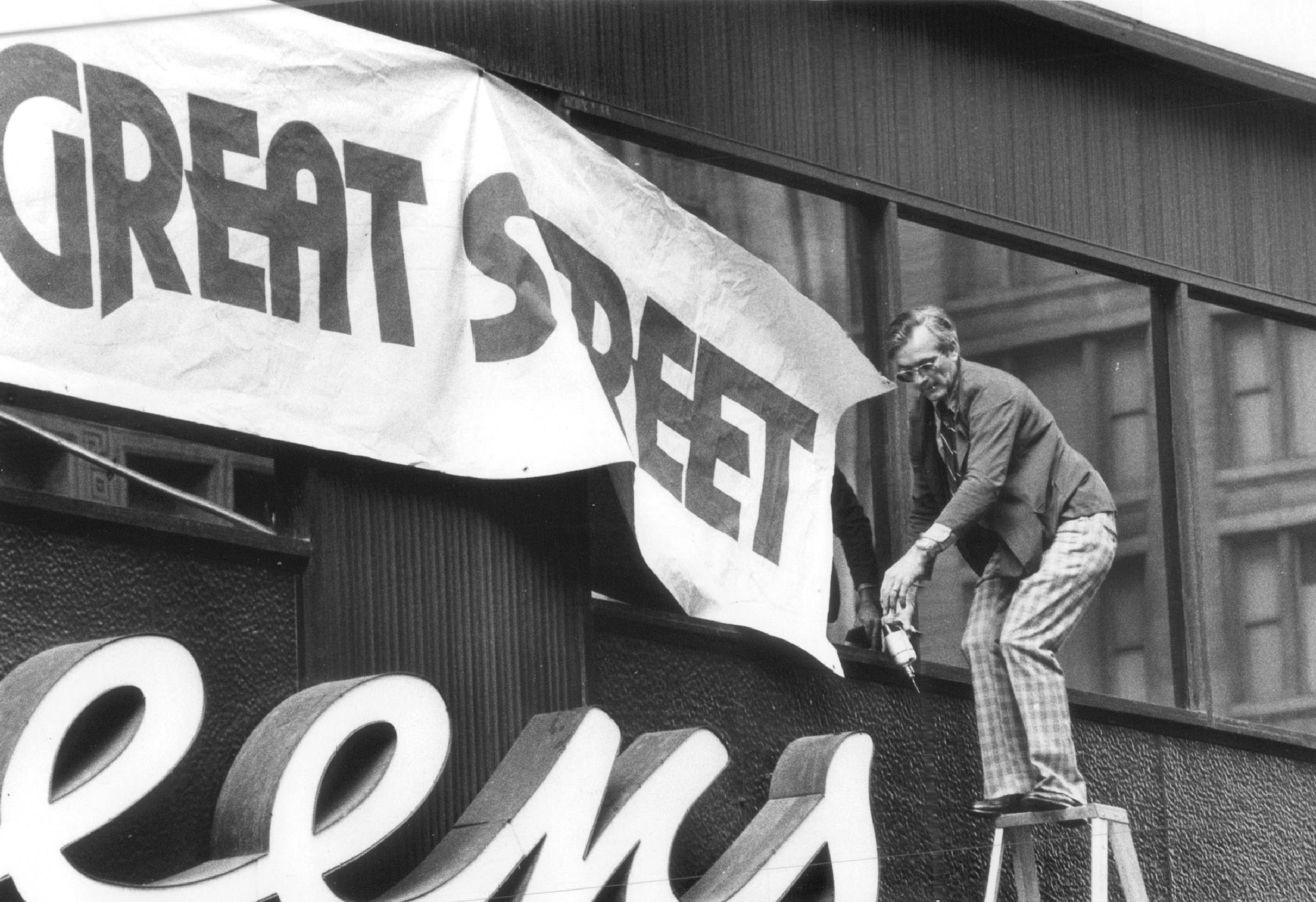 "A worker hangs a banner outside the downtown Walgreen's on State Street — that ""great street"" — in 1979."