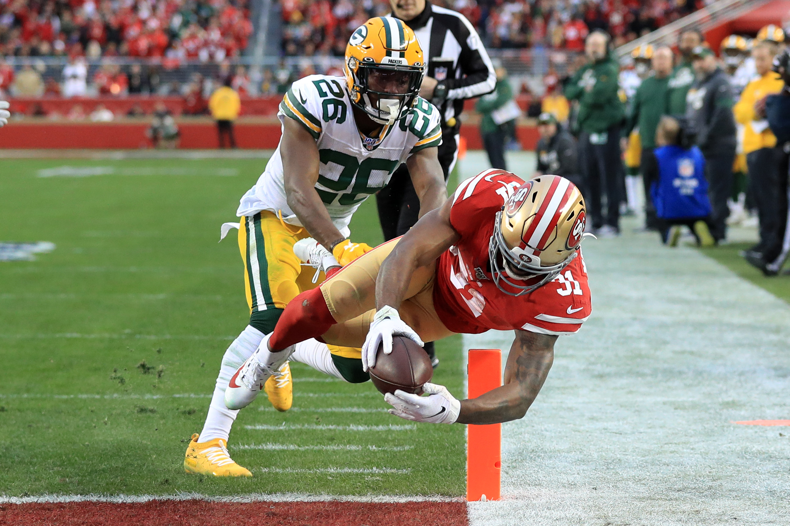 Raheem Mostert of the San Francisco 49ers dives into the end zone for a touchdown against Darnell Savage of the Green Bay Packers in the first half during the NFC Championship game at Levi's Stadium on January 19, 2020 in Santa Clara, California.