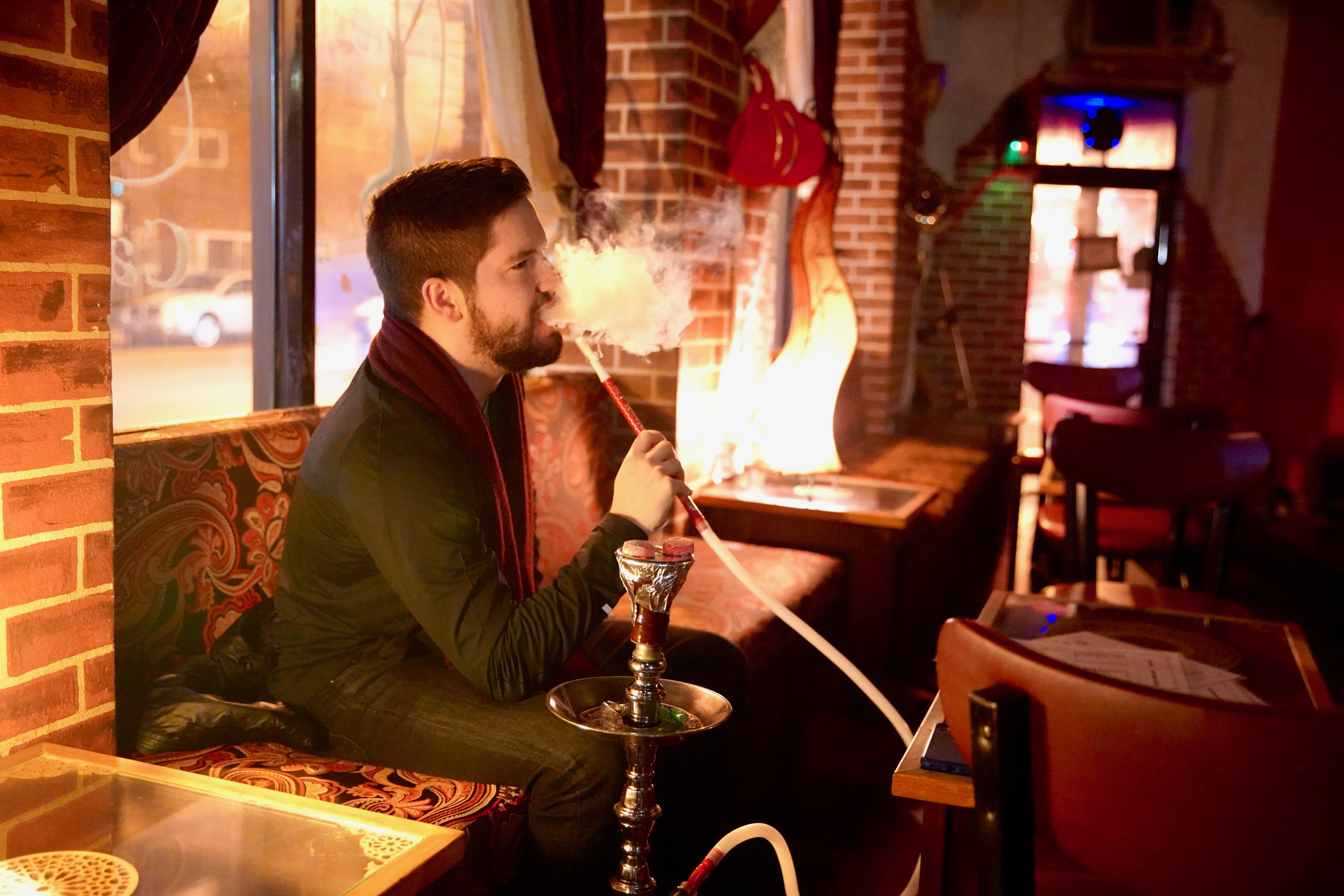 Brandon Wator, 26, smokes a hookah Wednesday, Jan. 15, 2020 at Arabia Cafe Hookah Lounge in Noble Square.