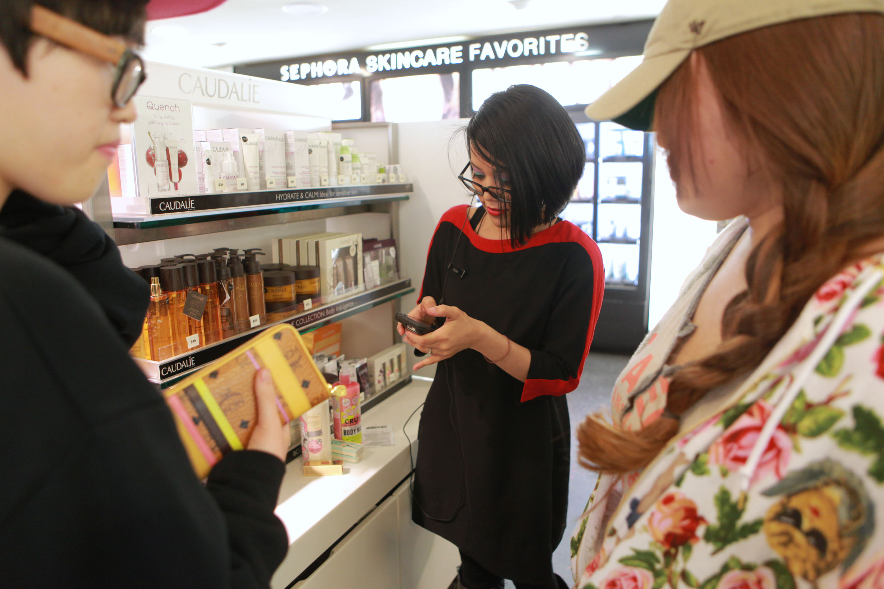 A Sephora employee assisting customers in a Sephora store.