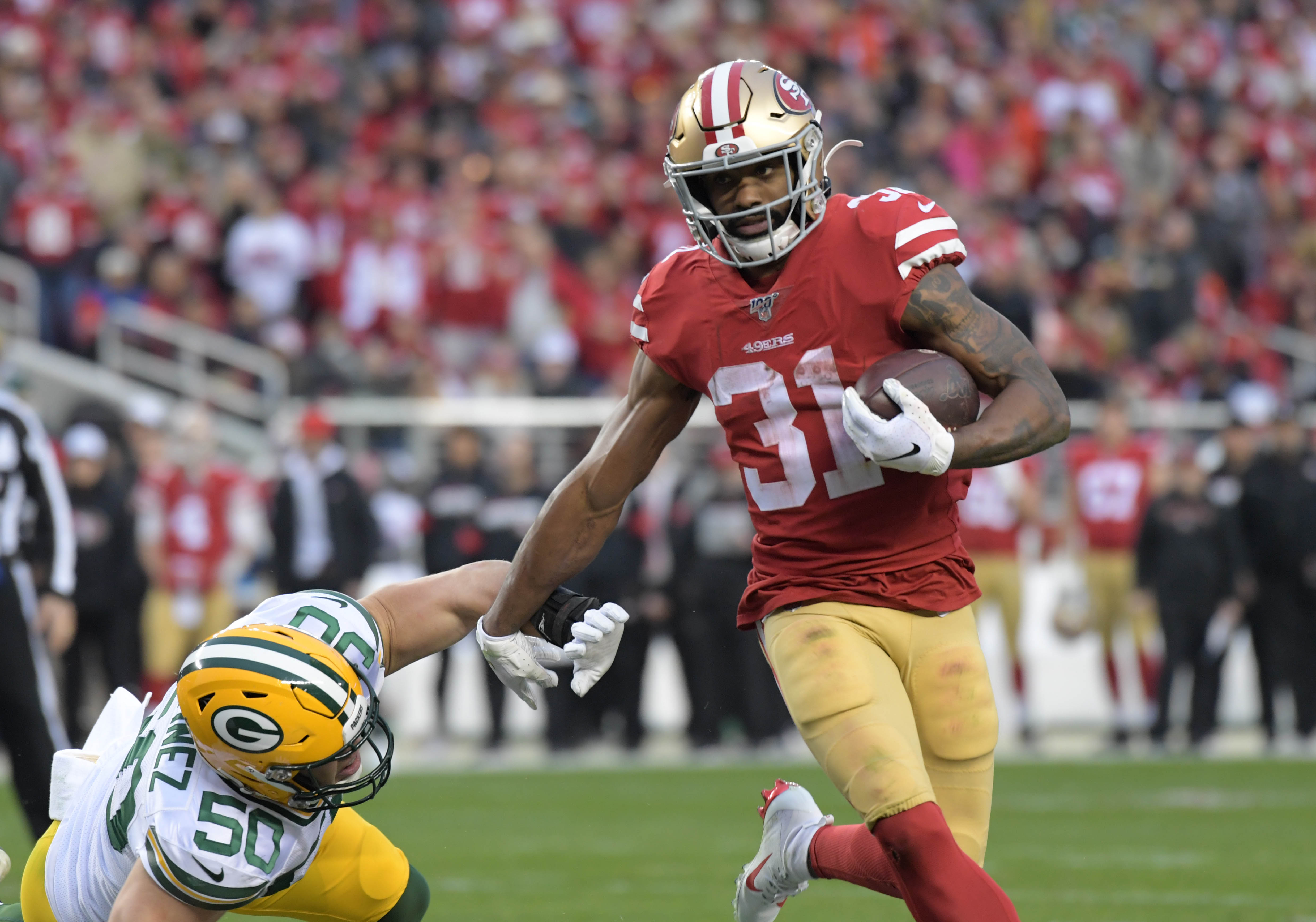 San Francisco 49ers running back Raheem Mostert runs past Green Bay Packers inside linebacker Blake Martinez in the second quarter of the NFC Championship Game at Levi's Stadium.
