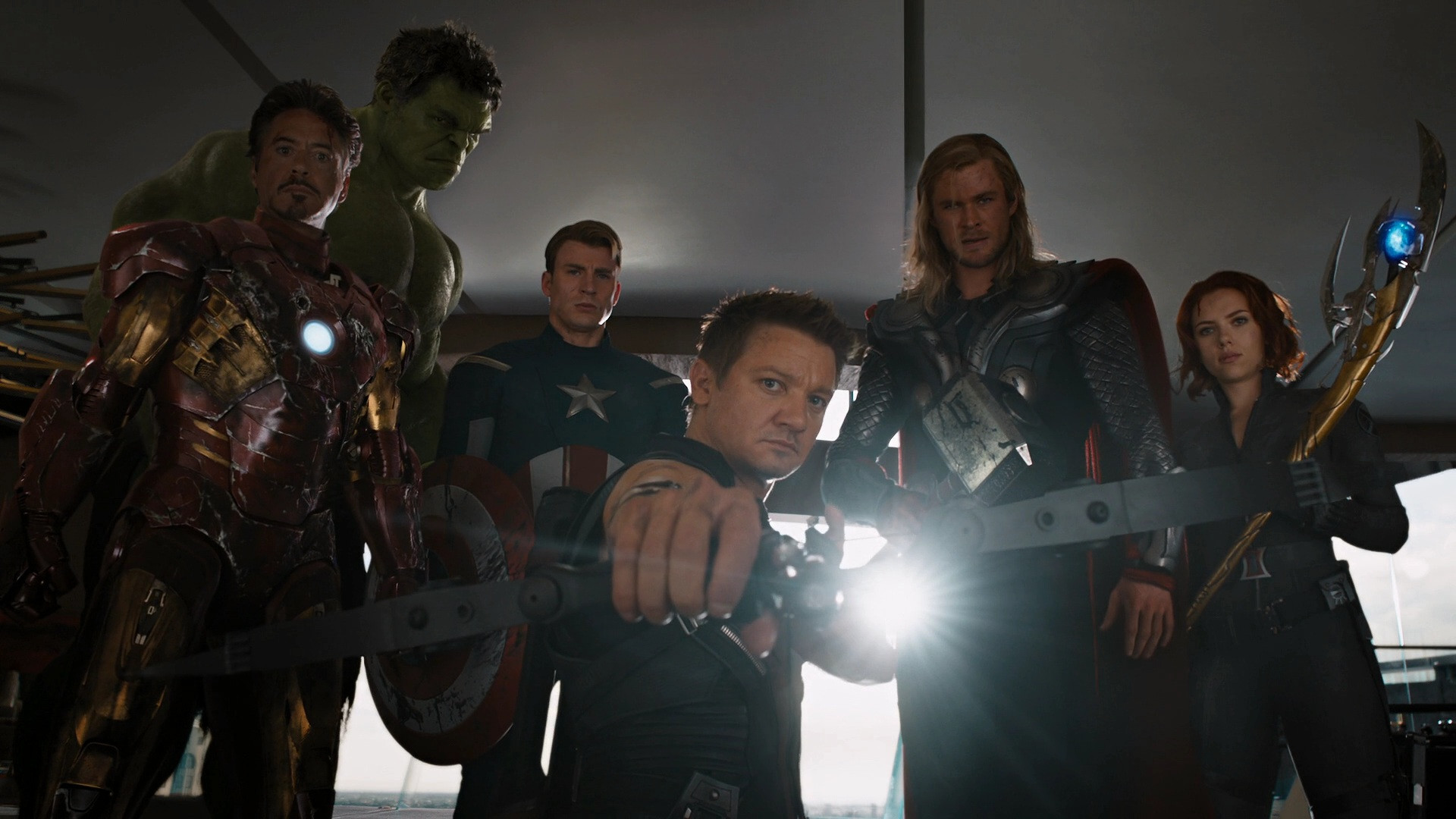 The Avengers pose around Loki with their weapons drawn