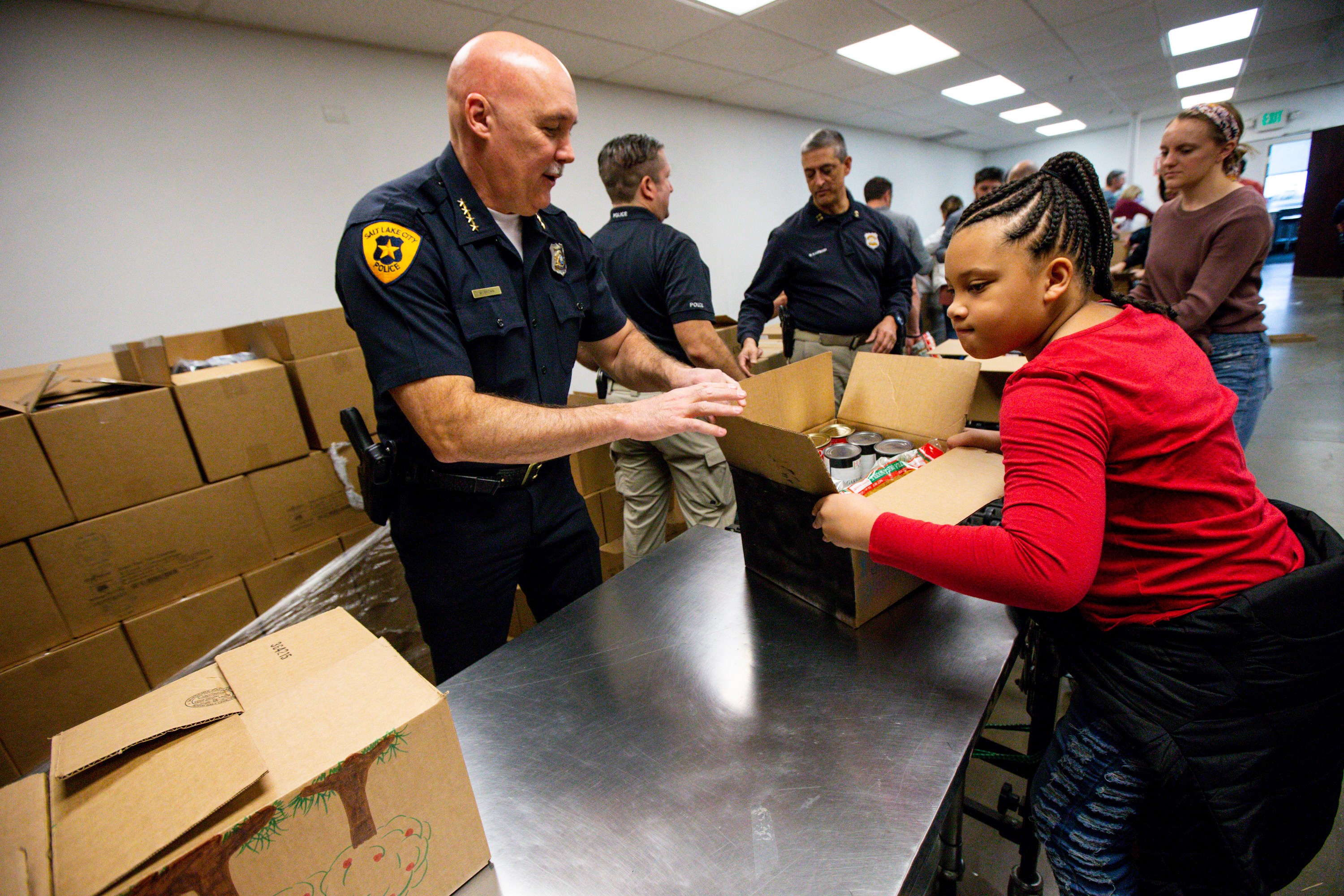 Salt Lake Police Chief Mike Brown and KaNiyah Lynch help fill boxes of food during the Martin Luther King Jr. Day of Service at the Utah Food Bank in South Salt Lake on Monday, Jan. 20, 2020. The volunteers helped fill 432 boxes, which will later be distributed to homebound seniors, homeless persons and others in need.