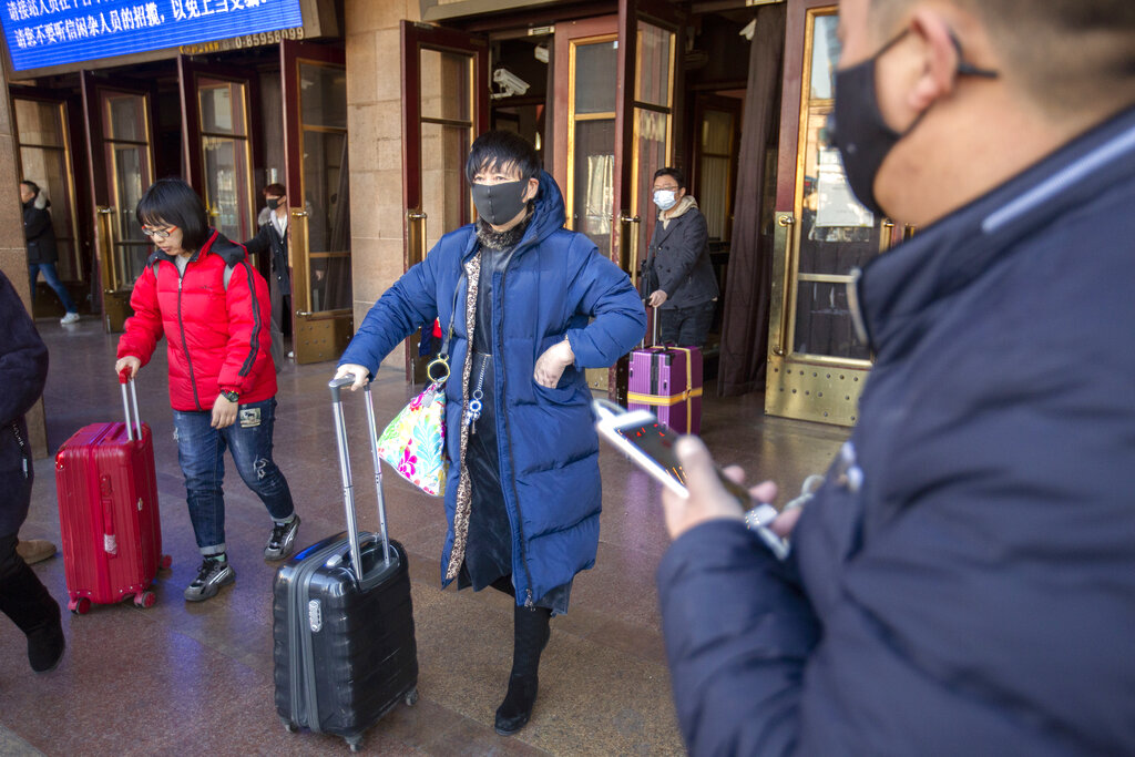 Travelers wear face masks as they walk outside of the Beijing Railway Station in Beijing