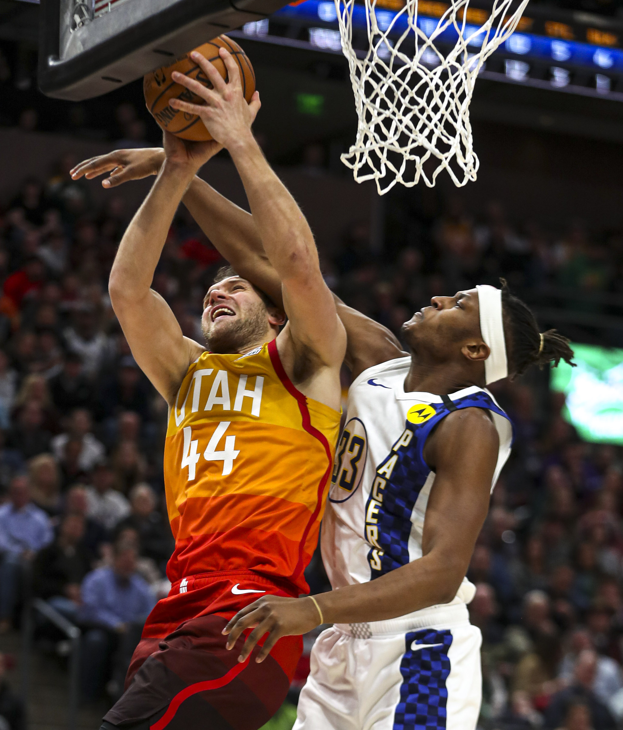 Utah Jazz forward Bojan Bogdanovic (44) gets fouled by Indiana Pacers center Myles Turner (33) during an NBA basketball game at Vivint Arena in Salt Lake City on Monday, Jan. 20, 2020.