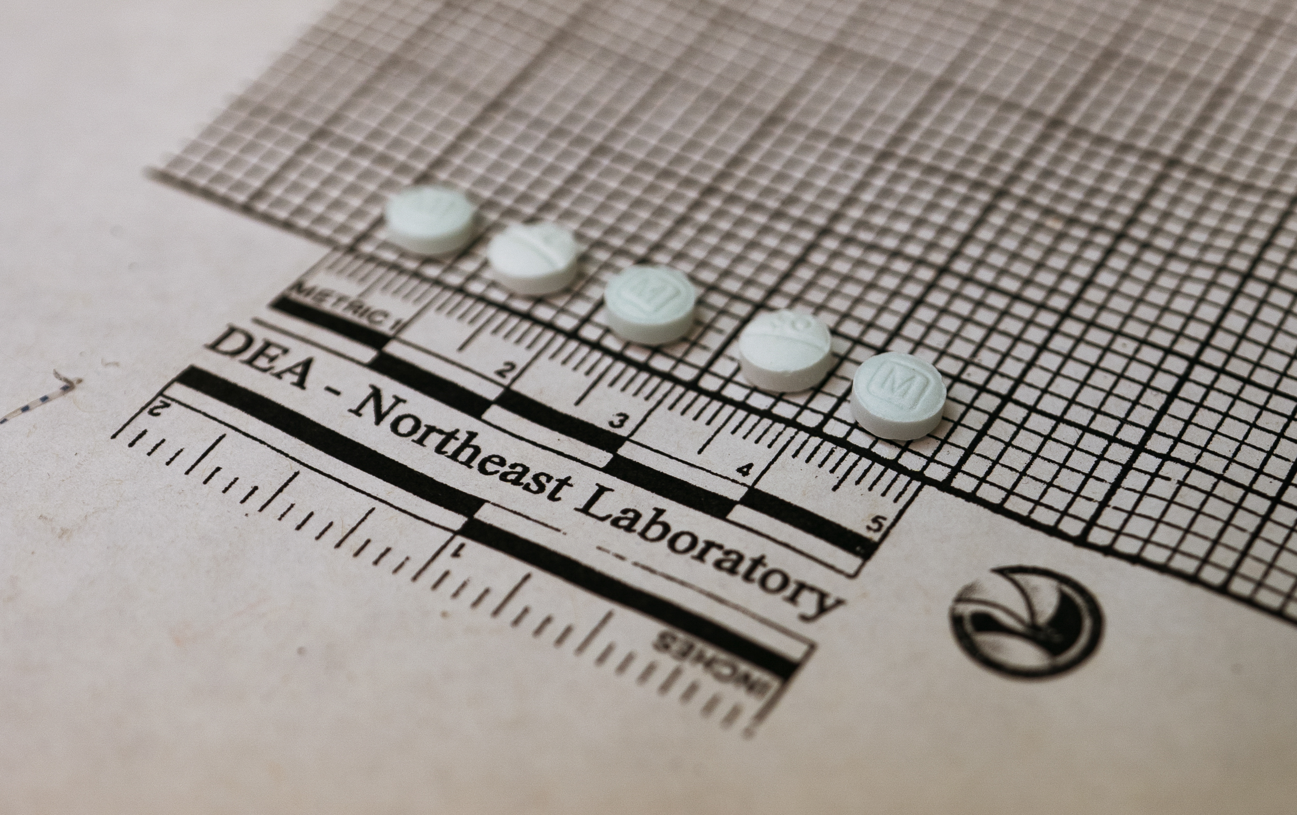 "Five small round pills lined up atop graph paper that reads, ""DEA - Northeast Laboratory."""