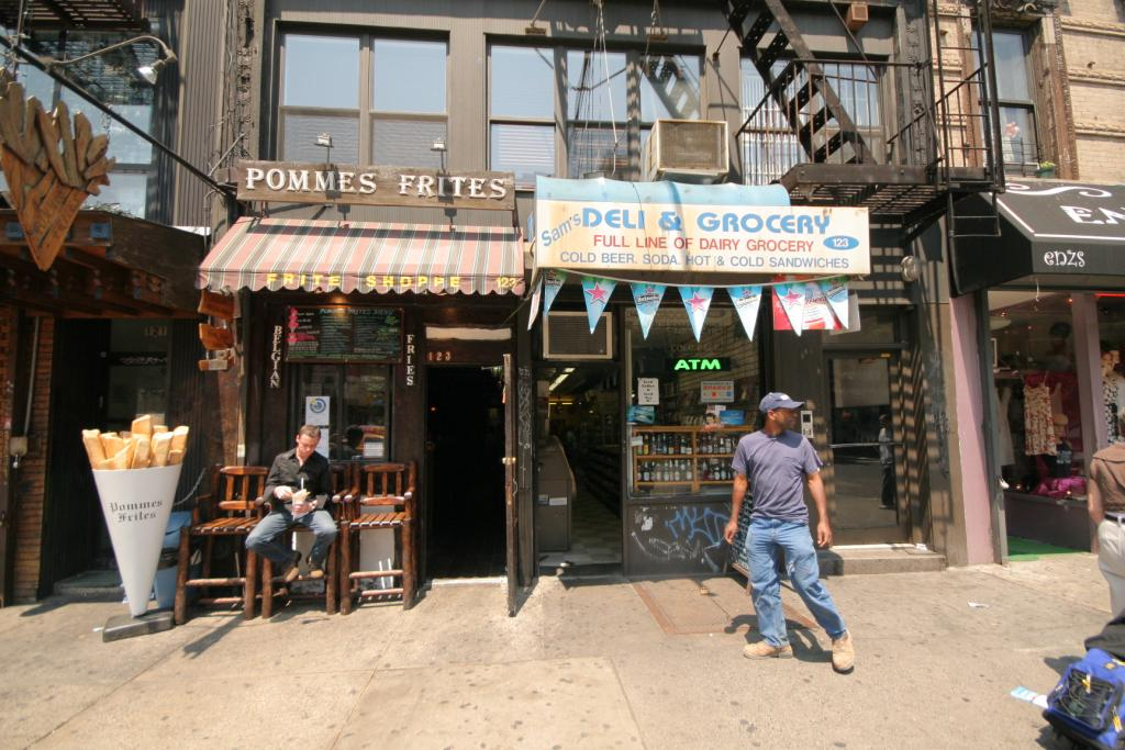 The exterior of restaurant Pommes Frites. A man is sitting on a bench in front of it eating, another man is walking by.