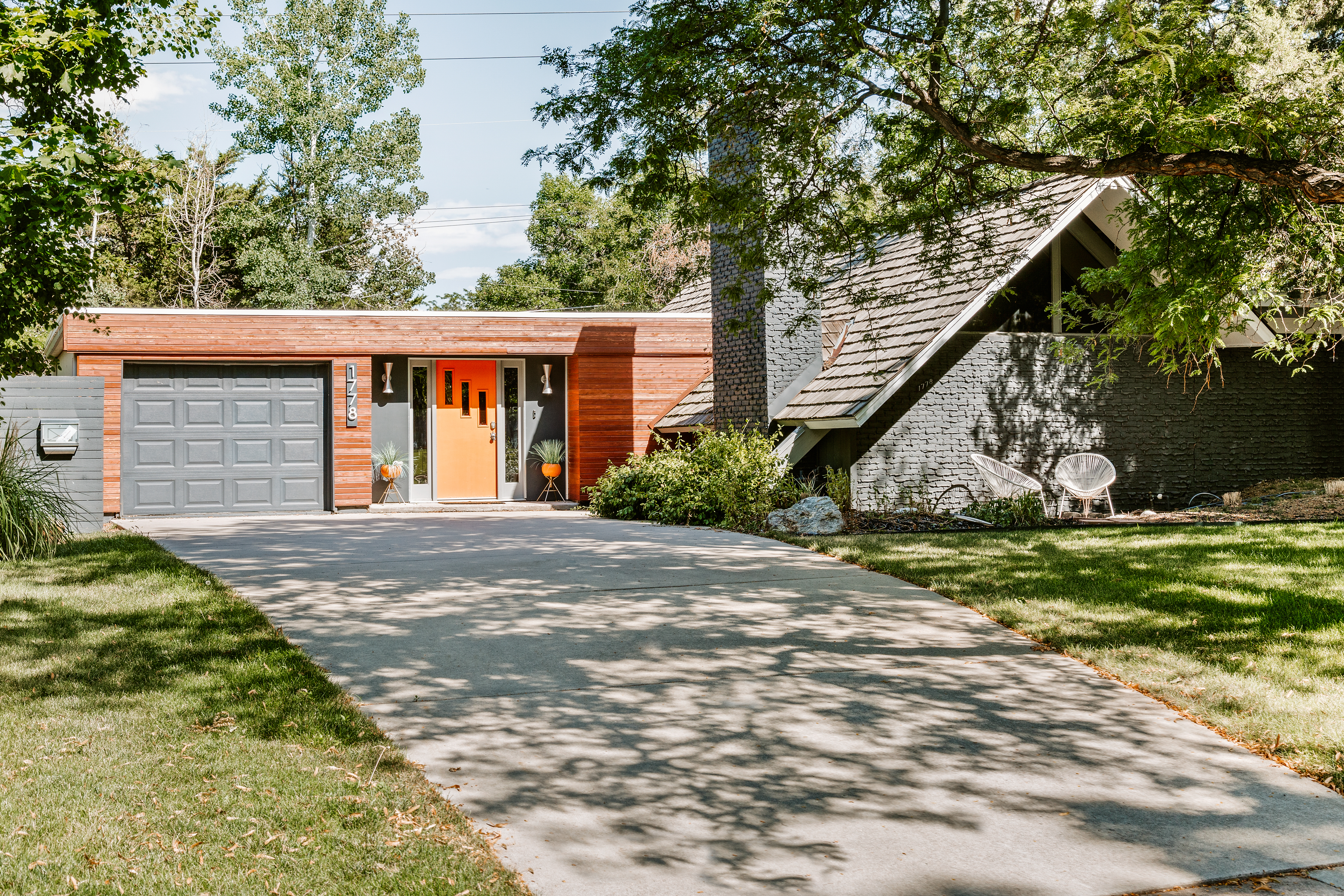 An exterior view of a midcentury home with a bright orange door, long driveway leading up to a two-car garage, and pitched A-frame style roof on the right.