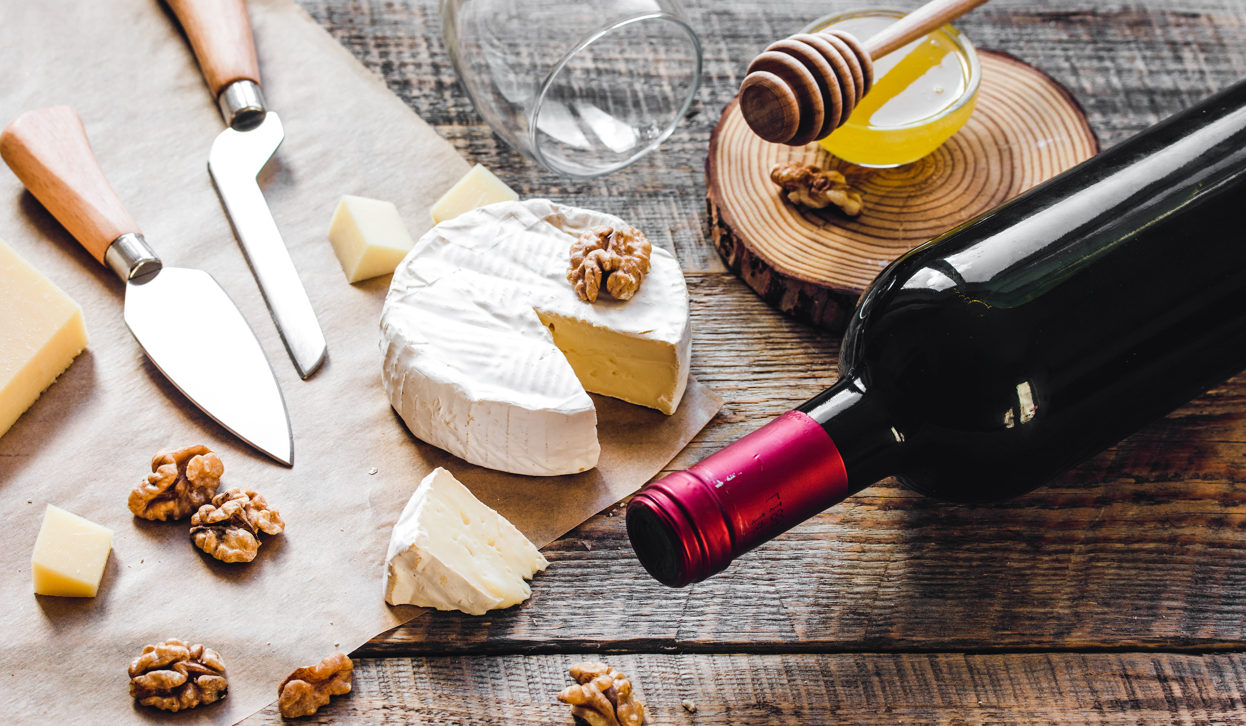 A spread of cheese, honey, and a wine bottle.