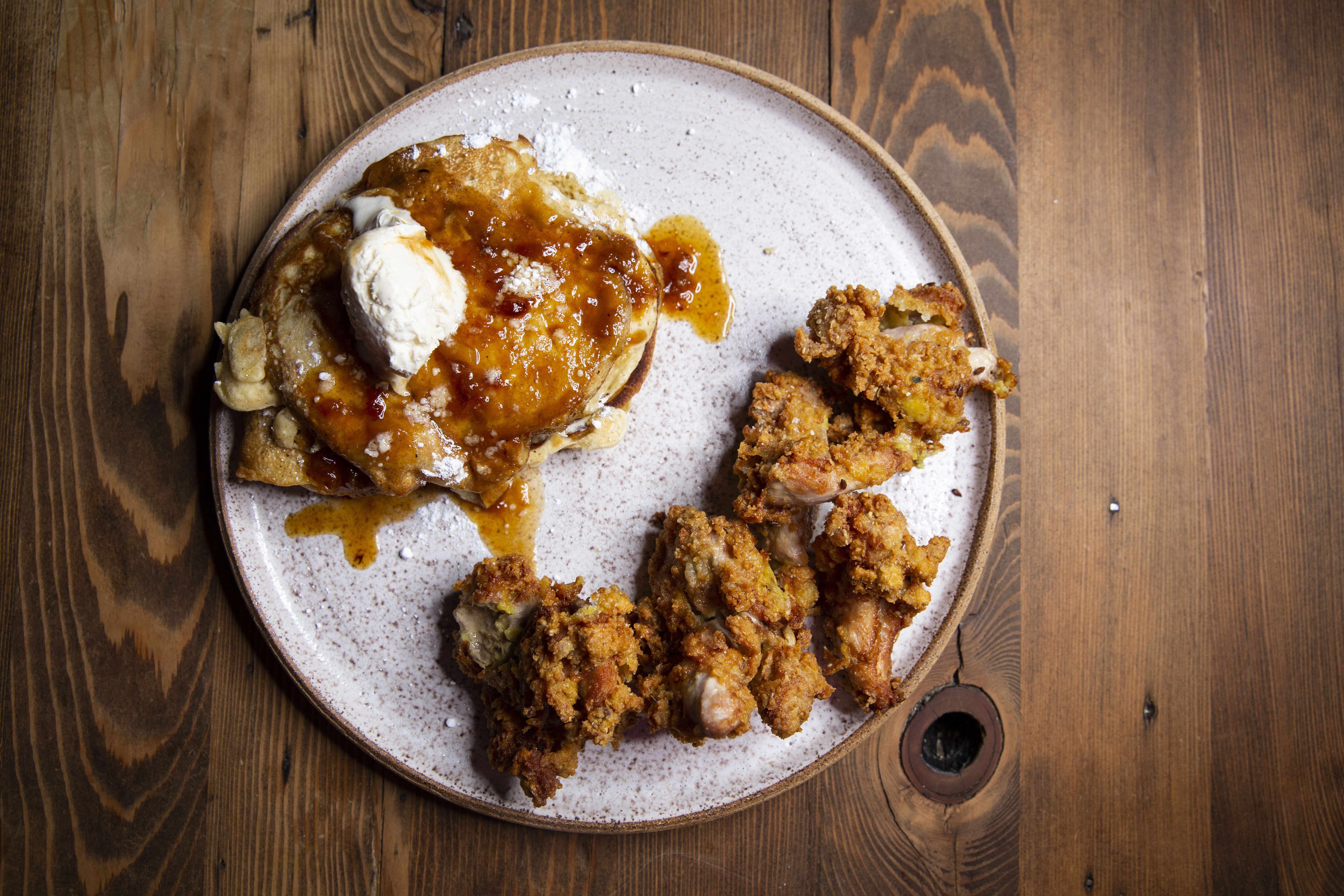 A plate with a stack of hoecakes and fried chicken, on a wooden table.