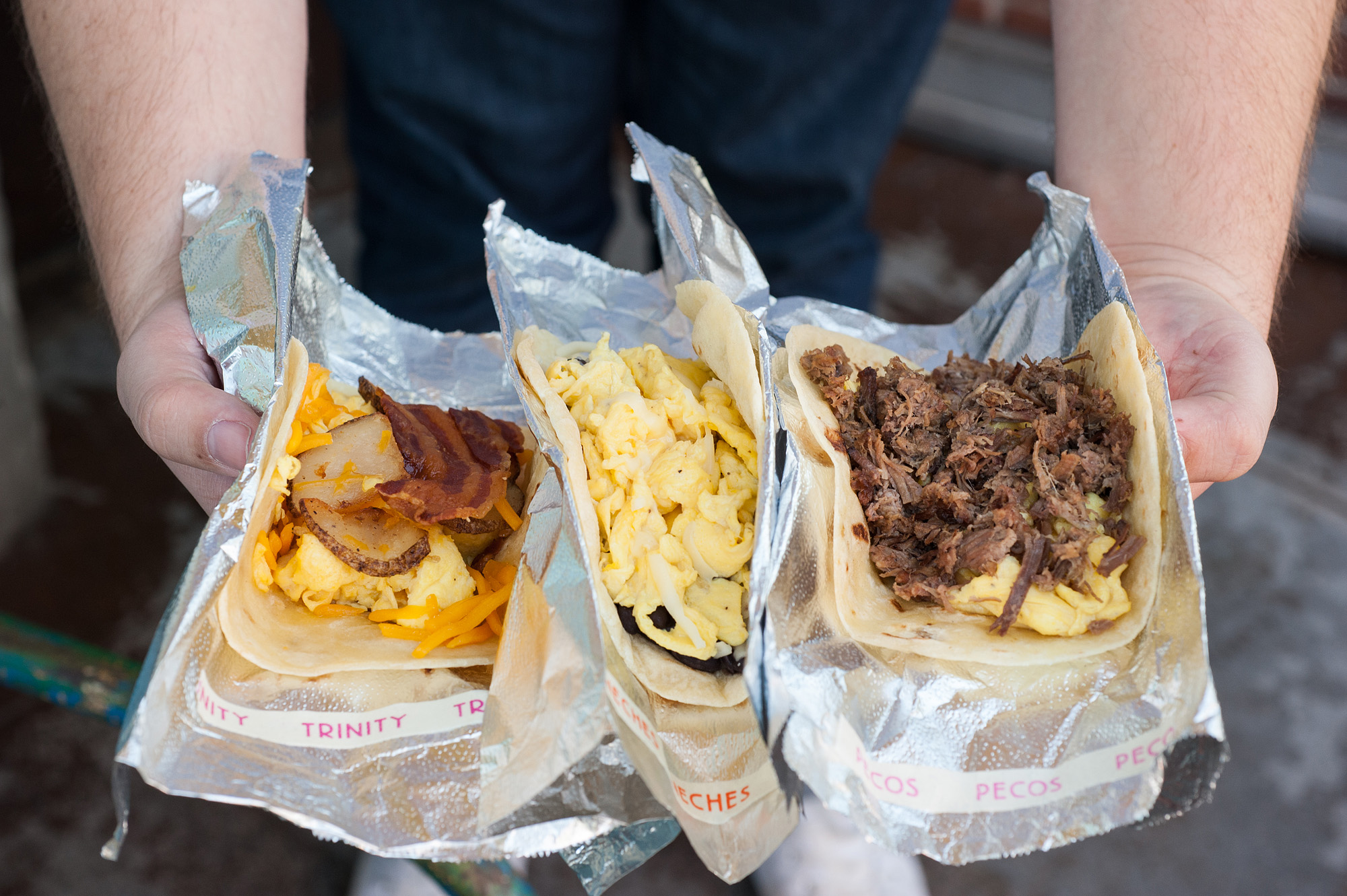 A person holds three different breakfast tacos from HomeState, wrapped in tin foil.