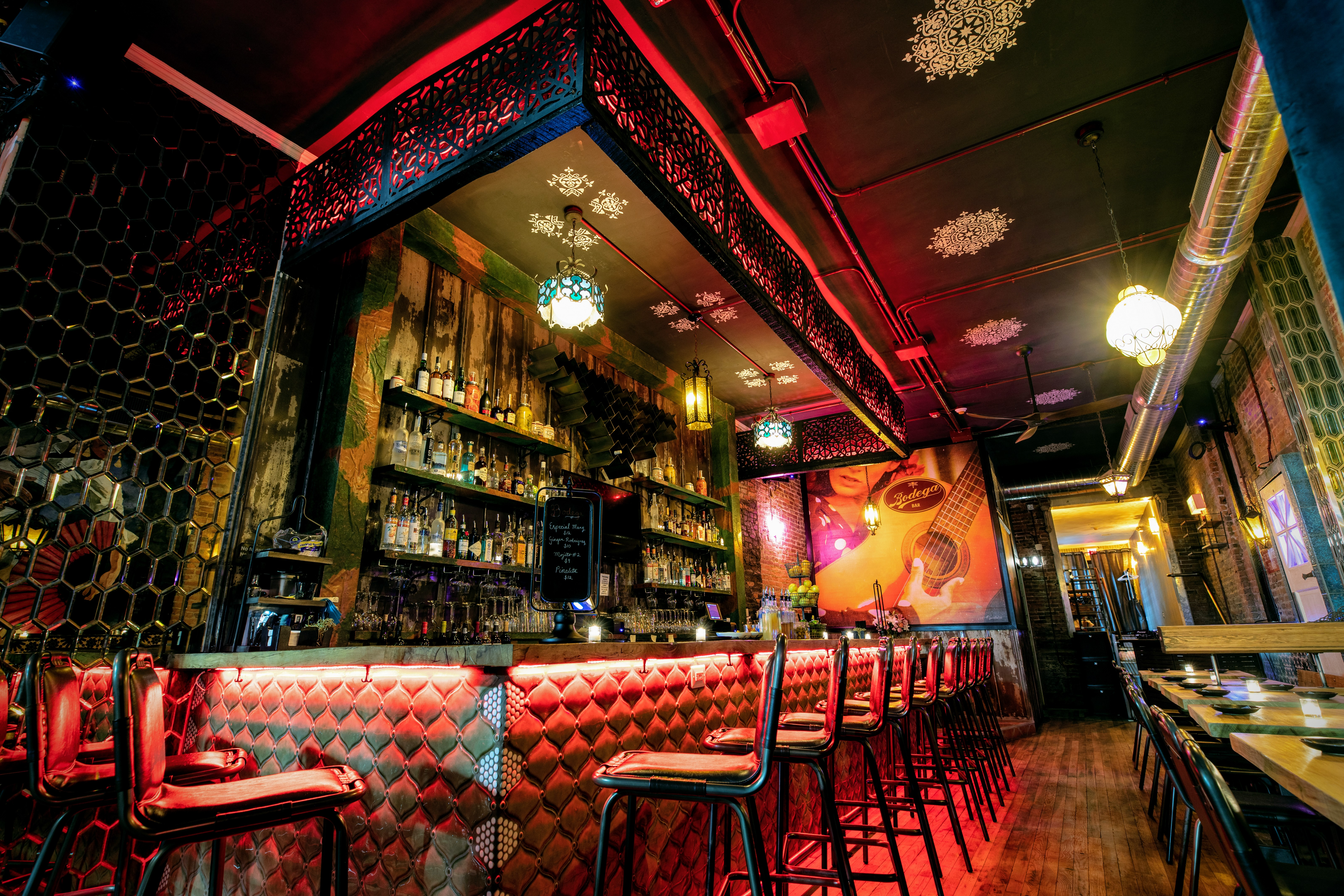 red-lit bar with row of stools and mural on the wall