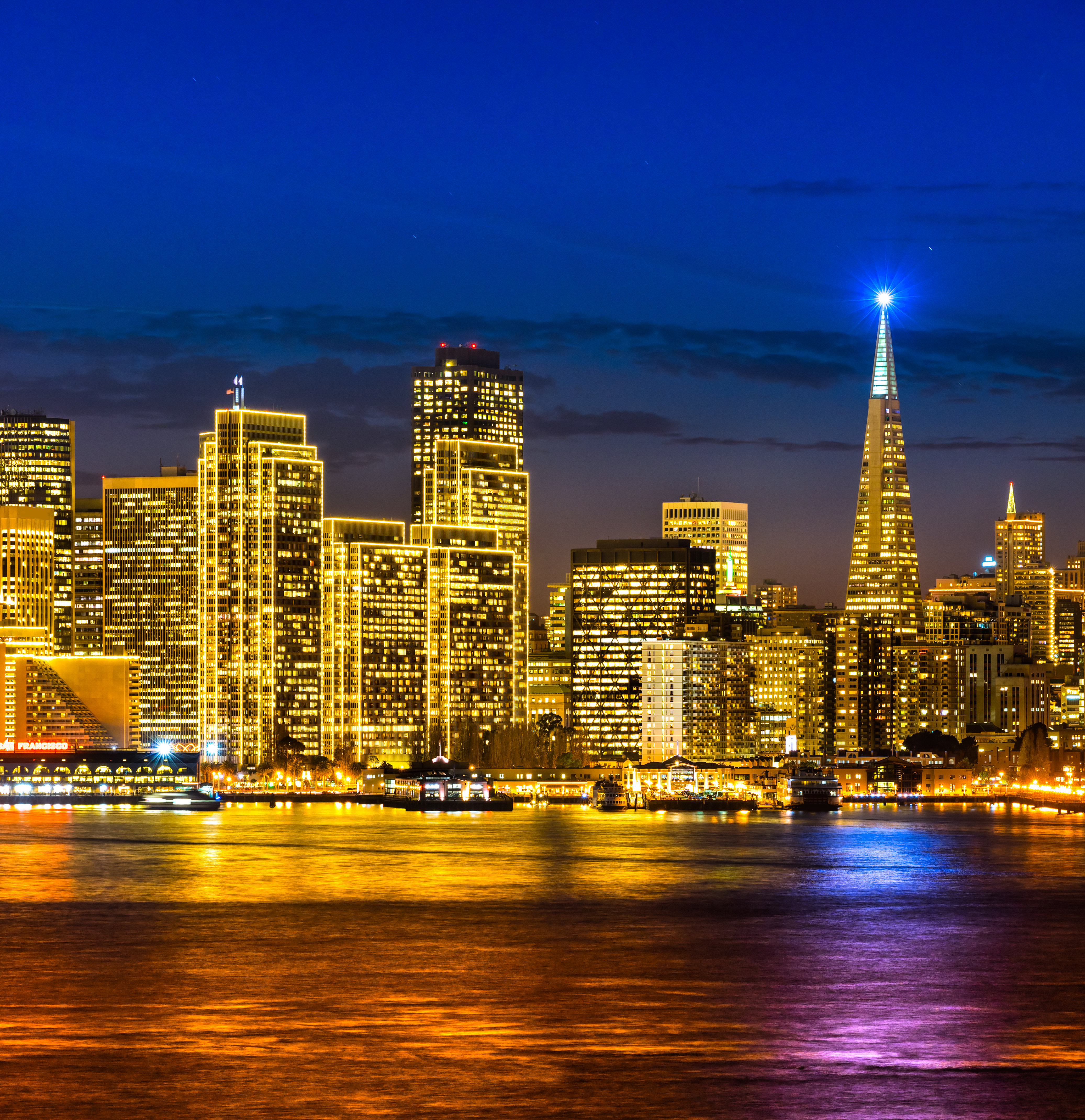 Tall buildings glowing with window lights in San Francisco, including a tall building with a pointed top and an almost blinding white light at the tip.