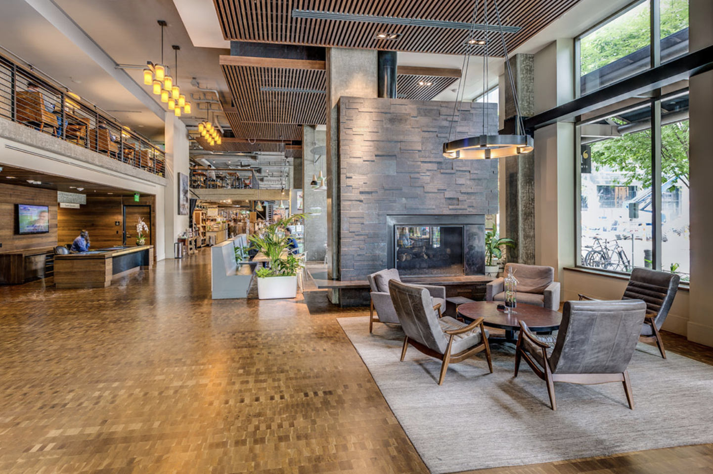 The light-filled lobby at Via6 Downtown, with modern furniture and retail spaces in the background.