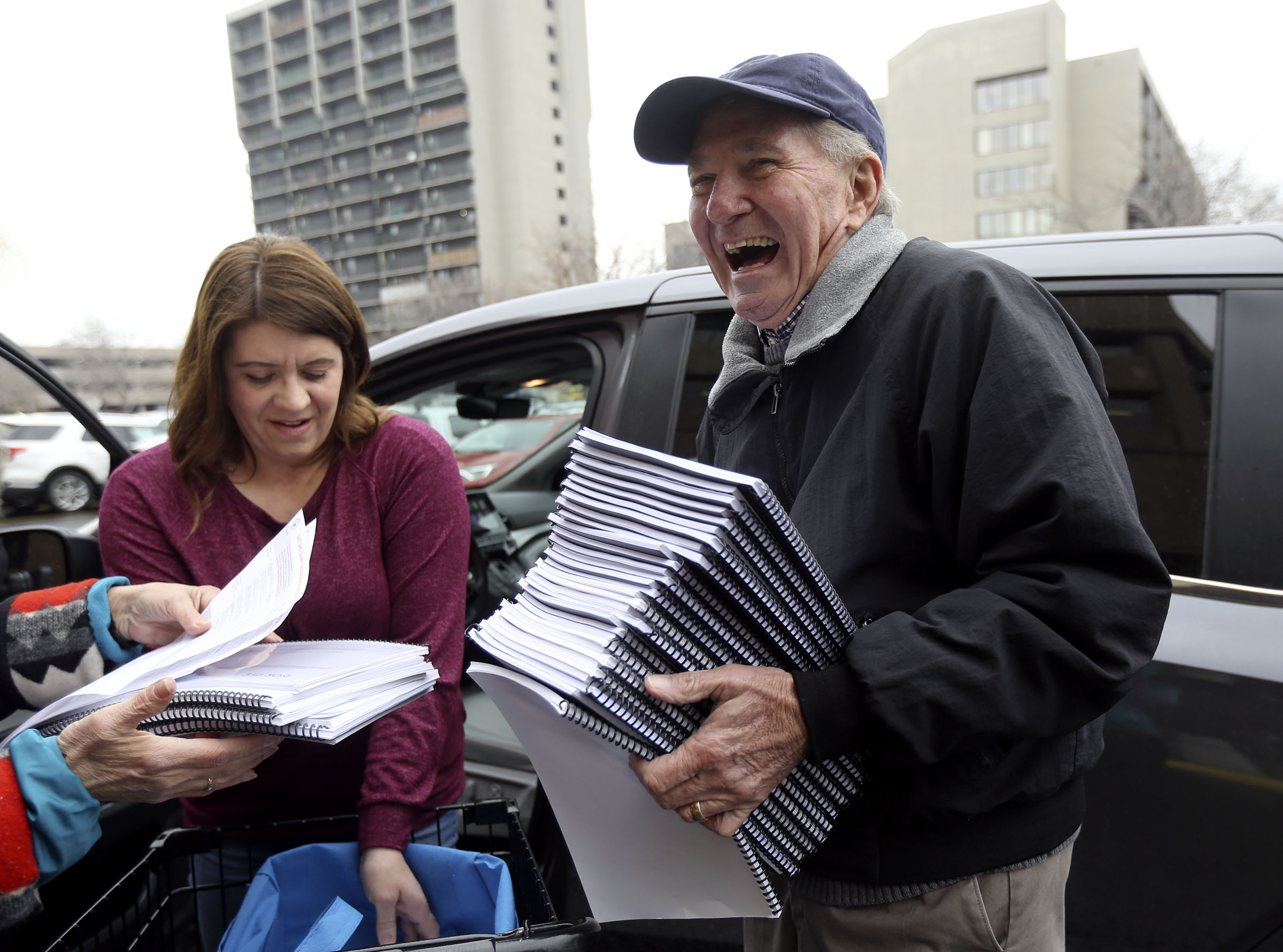 Kent Jorgenson, right, collects packets of signatures for the Utah tax referendum from Kimberly Bekmezian outside of the Salt Lake County Government Center in Salt Lake City on Tuesday, Jan. 21, 2020.